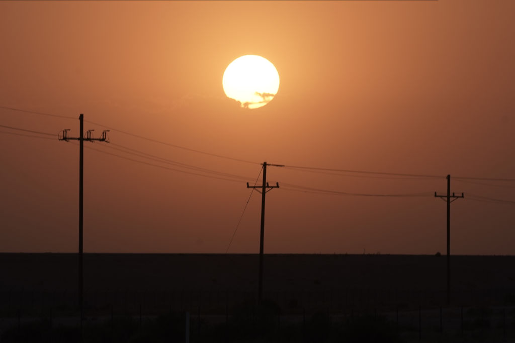 The sun rises over power lines near Imperial, California, on Tuesday, Aug. 18, 2020. California is bracing for another round of rolling blackouts Tuesday as unrelenting heat drives electricity demand to an all-time high, straining a power grid thats already been pushed to the brink of failure.