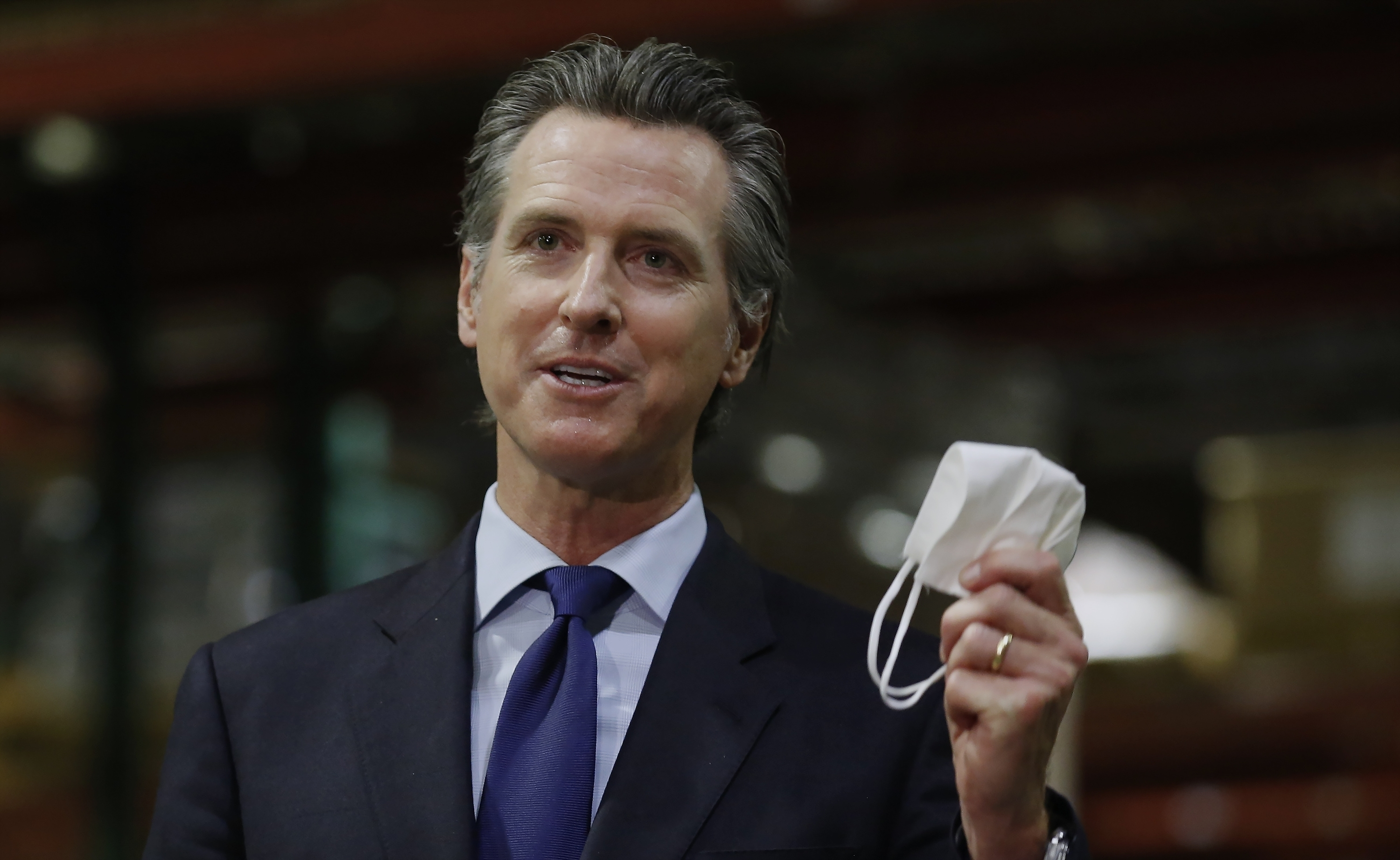 Gov. Gavin Newsom holds a face mask as he urges people to wear them to fight the spread of the coronavirus during a news conference in Rancho Cordova, Calif on June 26, 2020.