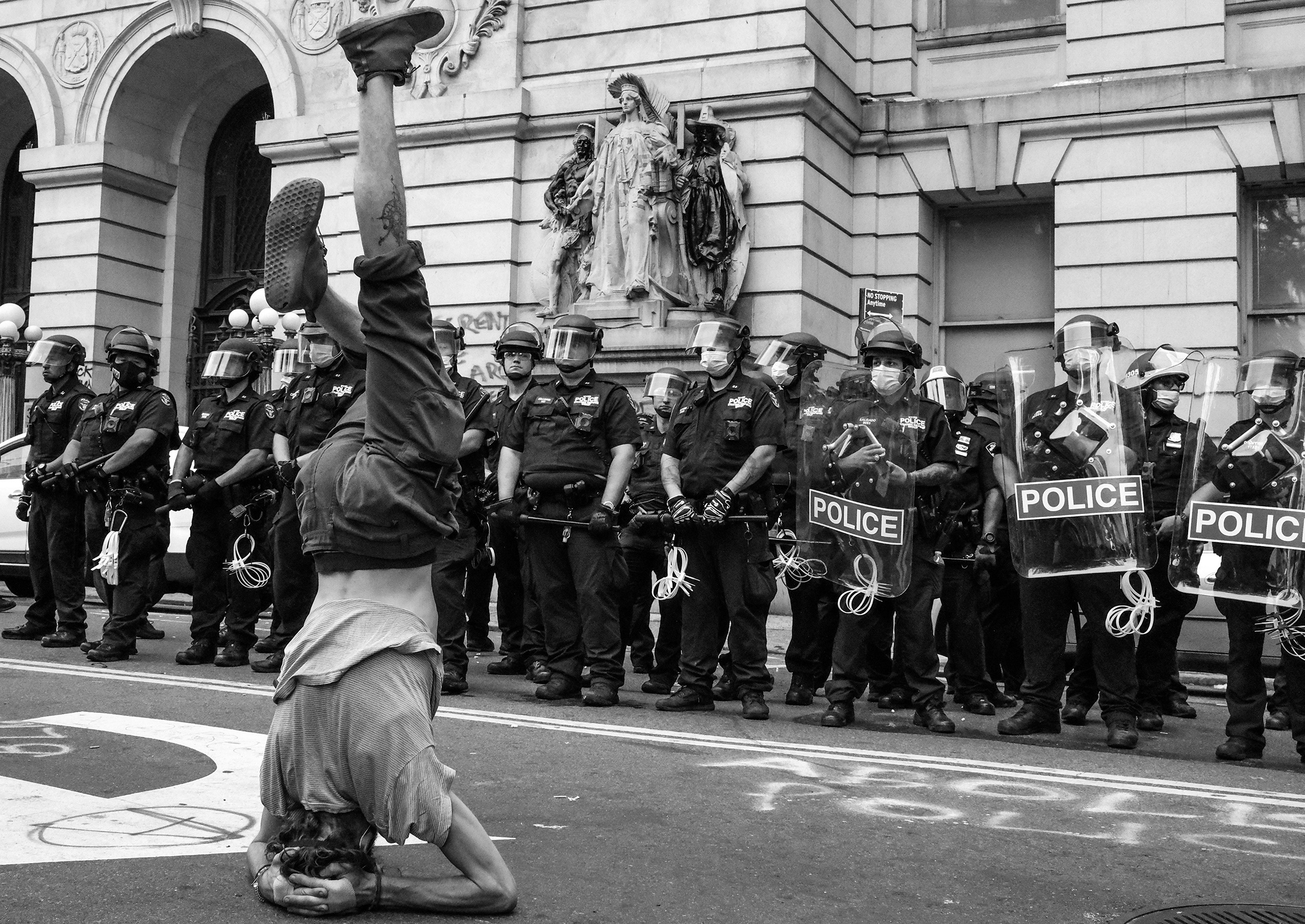 A protester stands on his head in front of a line of NYPD near City Hall during the first attempt to take over the so-called  Abolition Park,  a makeshift camp in City Hall Park made up of people protesting police brutality.
