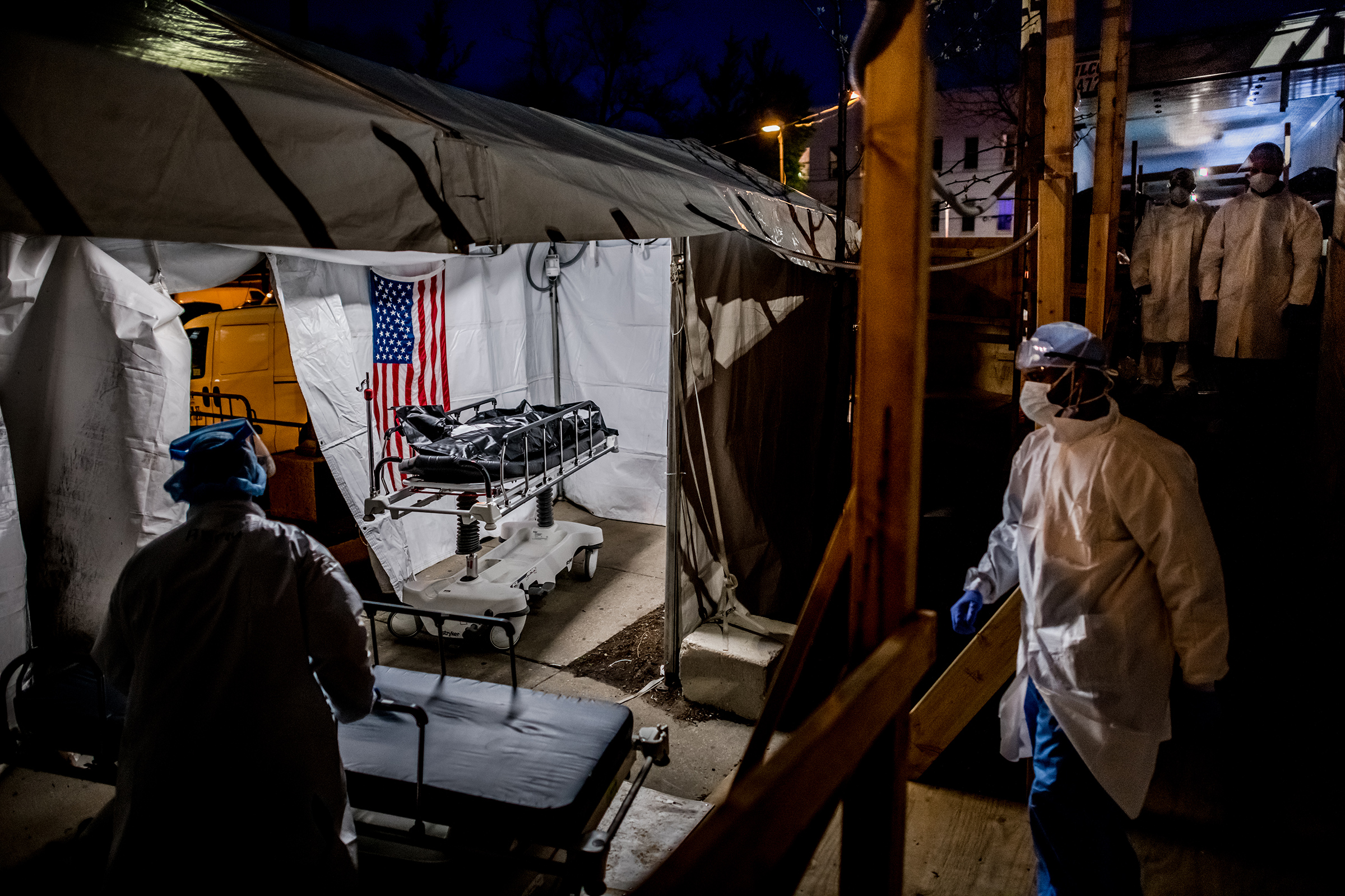 The transport team moves the body bags of deceased COVID-19 patients from the overflowing morgue of Brooklyn's Wyckoff Heights Medical Center into the improvised morgue set up outside on April 27. Three refrigerated semitrailers, capable of holding more than 150 bodies between them, were brought in as an emergency solution during the height of the pandemic. The transports often occurred at night to avoid upsetting neighbors of the hospital.