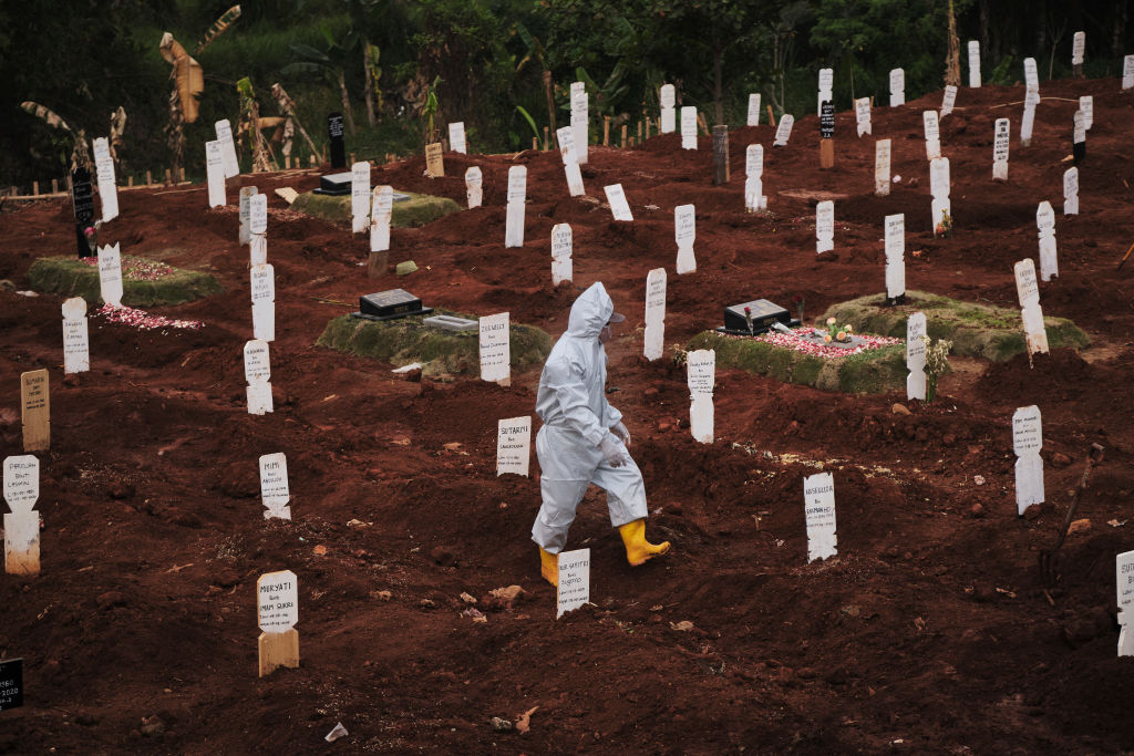 A municipal cemetery worker walks through  a special cemetery for suspected  Covid-19 victims on September 11, 2020 in Jakarta, Indonesia.
