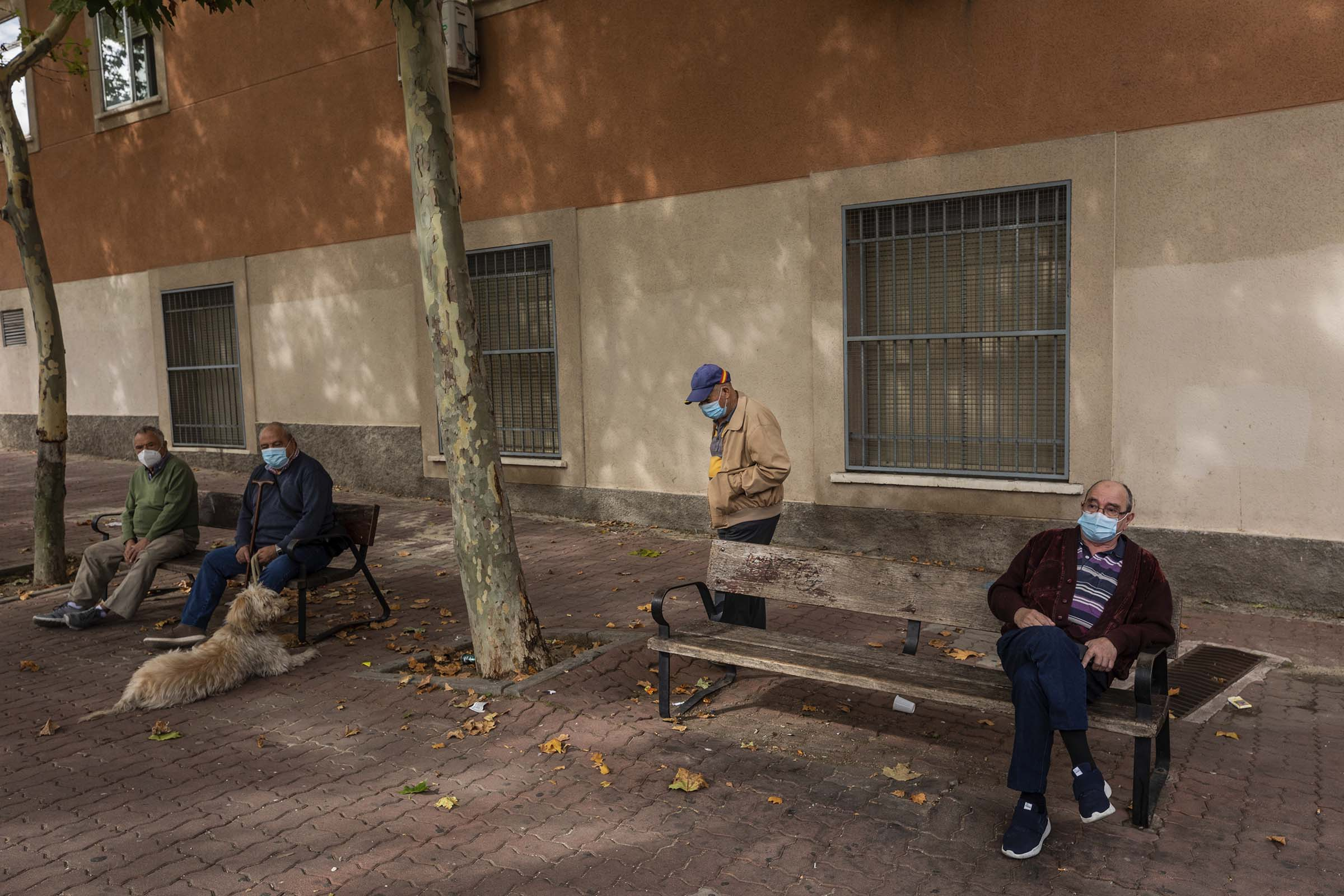 Elders wearing face masks to prevent the spread of the coronavirus sit on a park in Madrid, Spain, on Sept. 23, 2020.