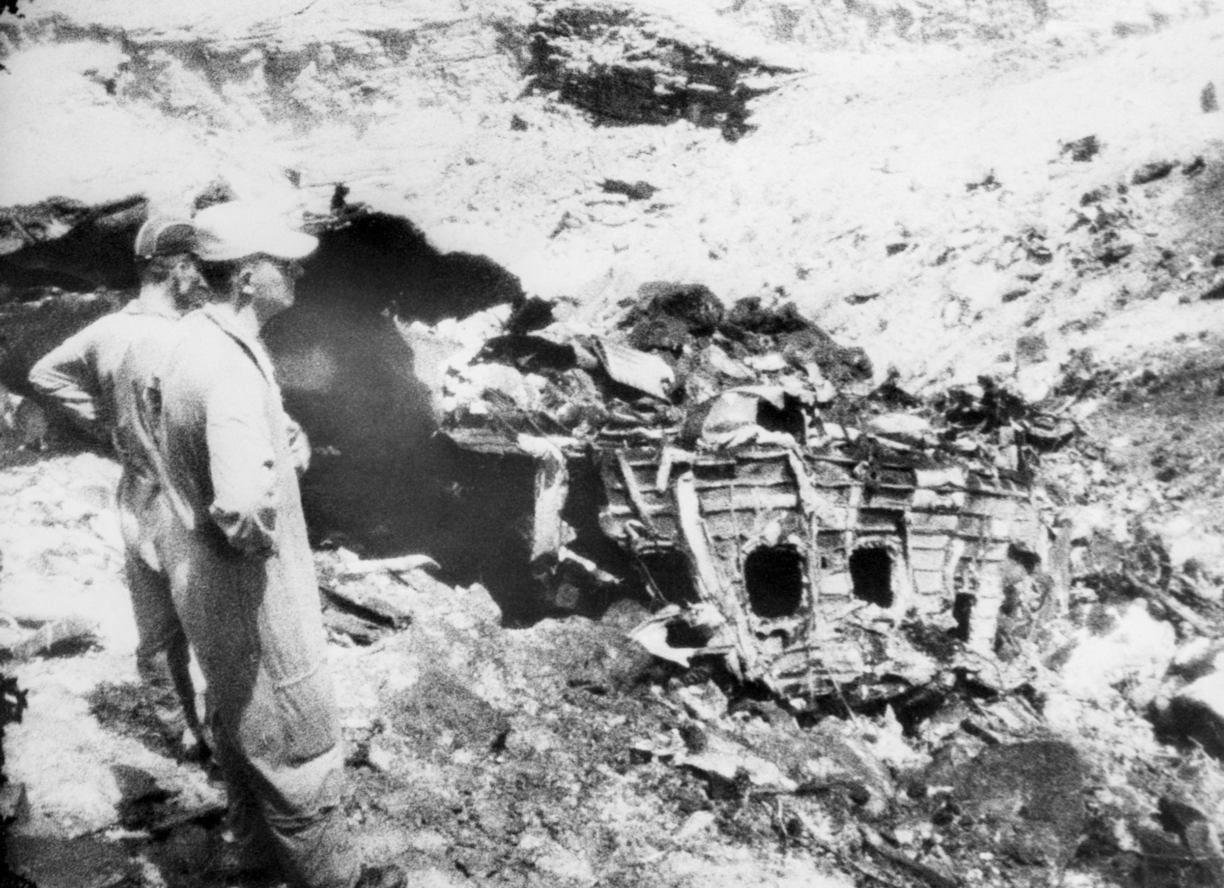 Two men from the rescue party looking at a section of the wrecked fuselage of the TWA Super constellation plane that crashed in the Grand Canyon, in July of 1956.