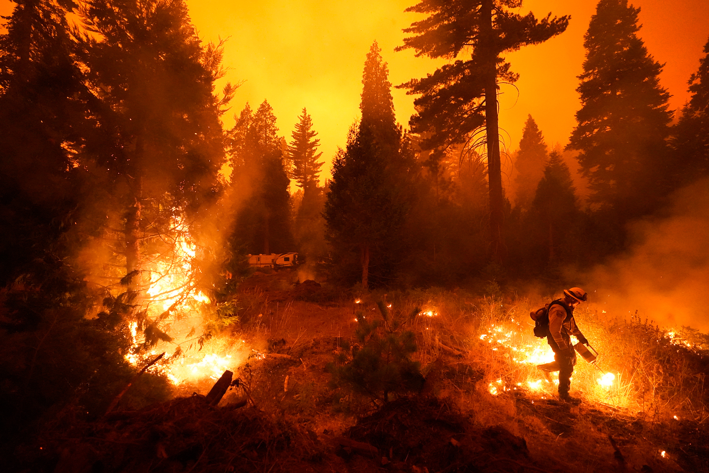 Firefighter Ricardo Gomez, part of a San Benito Monterey Cal Fire crew, sets a controlled burn with a drip torch while fighting the Creek Fire in Shaver Lake, Calif., on Sept. 6, 2020.