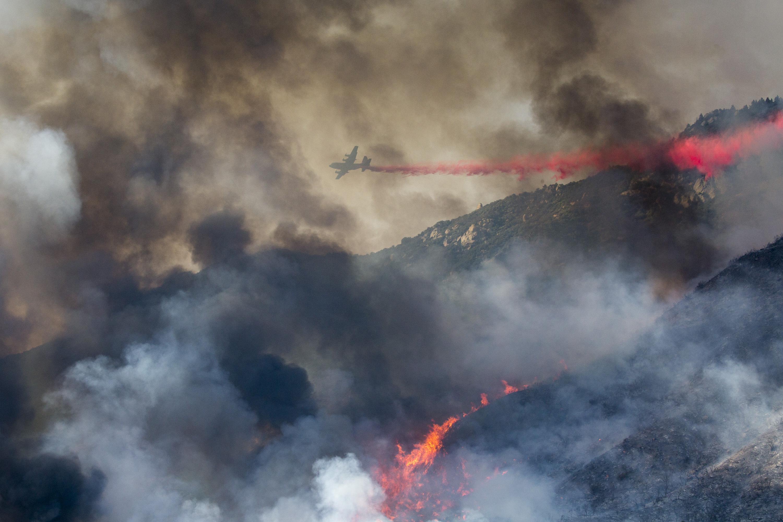 An air tanker drops retardant at a wildfire burns at a hillside in Yucaipa, Calif., Sept. 5, 2020.
