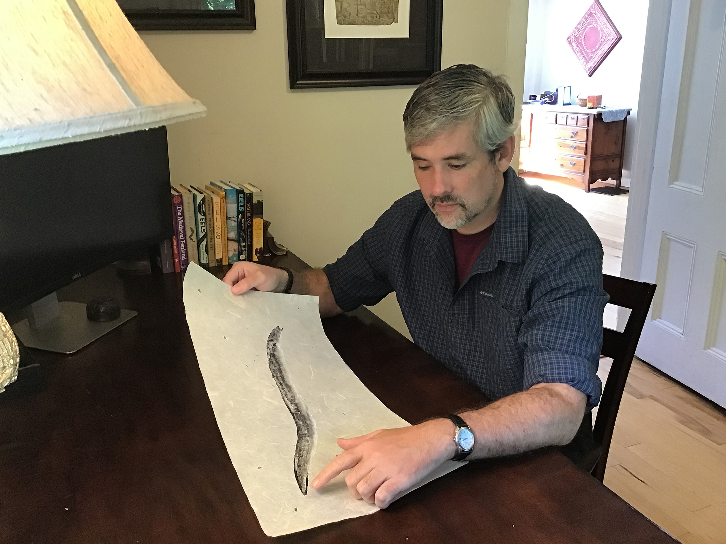 John Wyatt Greenlee looks at a gyotaku print of an eel by Bruce Koike in Sept.