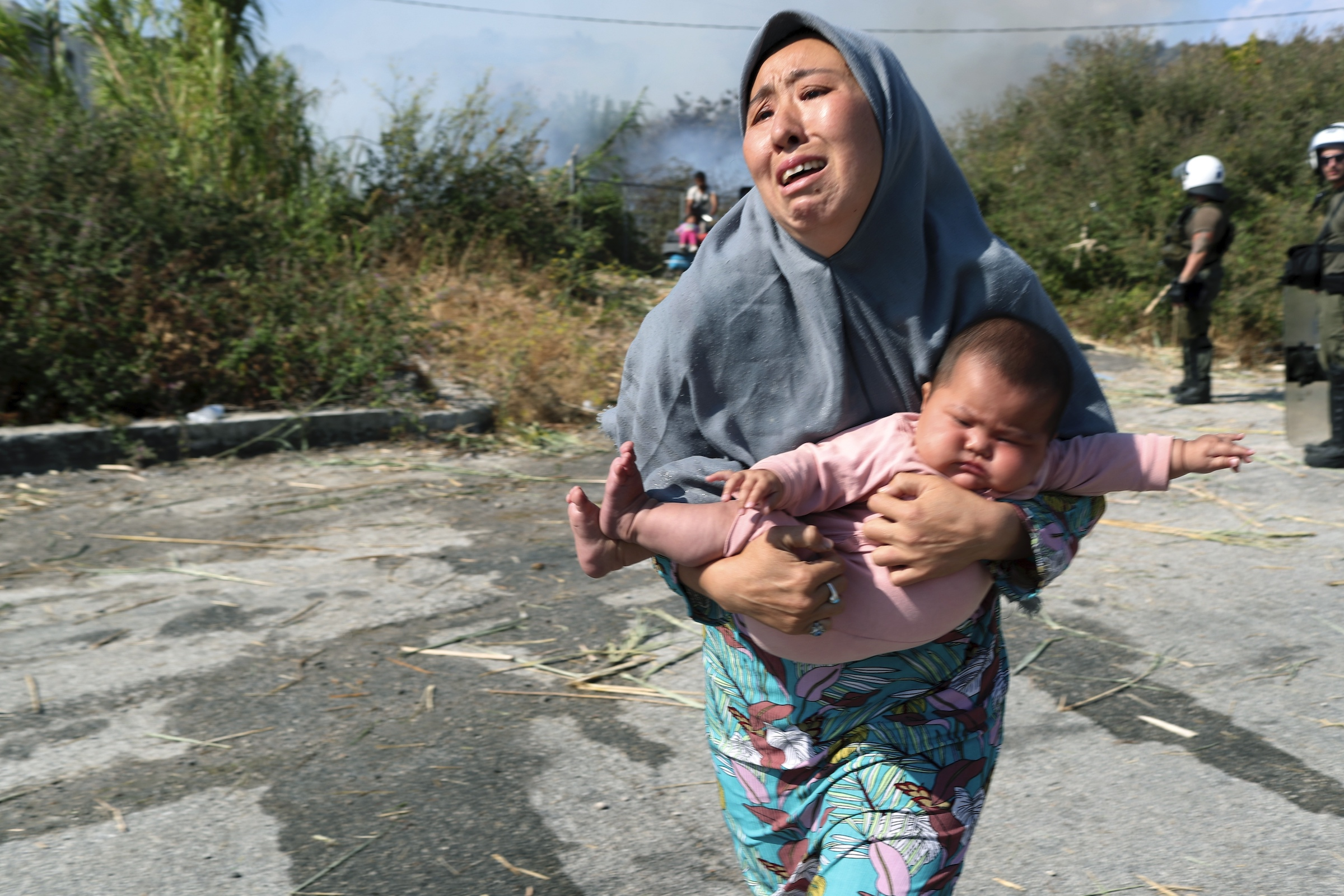 A migrant holds her baby as she runs to avoid a small fire in a field near Mytilene town, on the northeastern island of Lesbos, Greece, Sept. 12, 2020