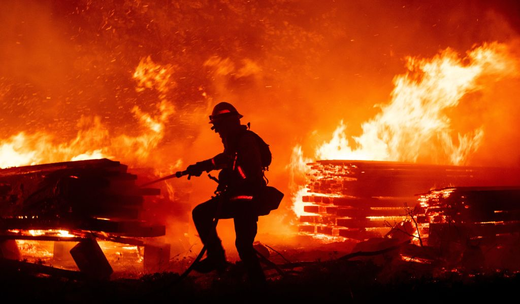 A firefighter douses flames as they push towards homes during the Creek fire in the Cascadel Woods area of unincorporated Madera County, California on Sept. 7, 2020.