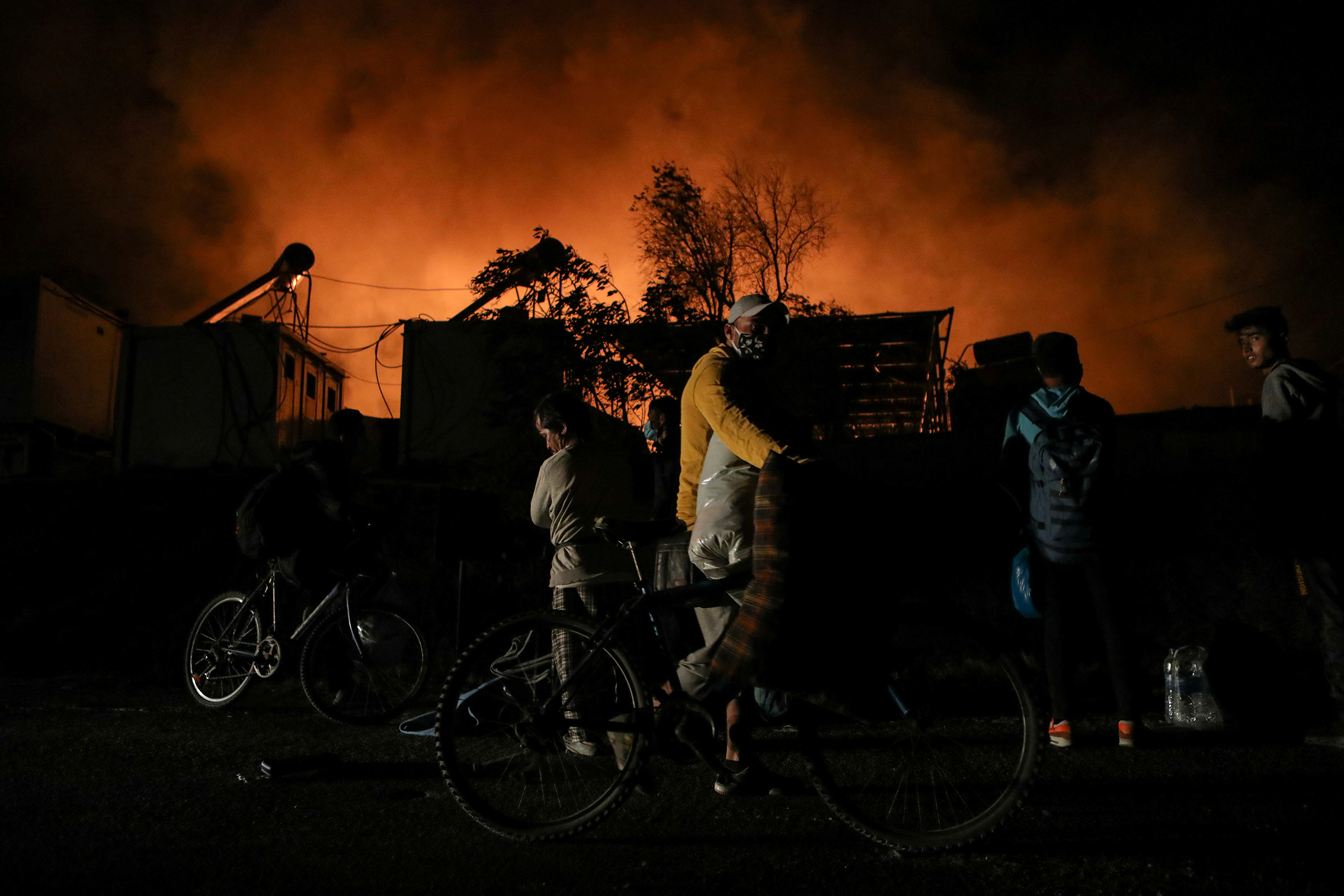 Refugees and migrants carry their belongings as they flee from a fire burning at the Moria camp on the island of Lesbos, Greece, on Sept. 9, 2020.