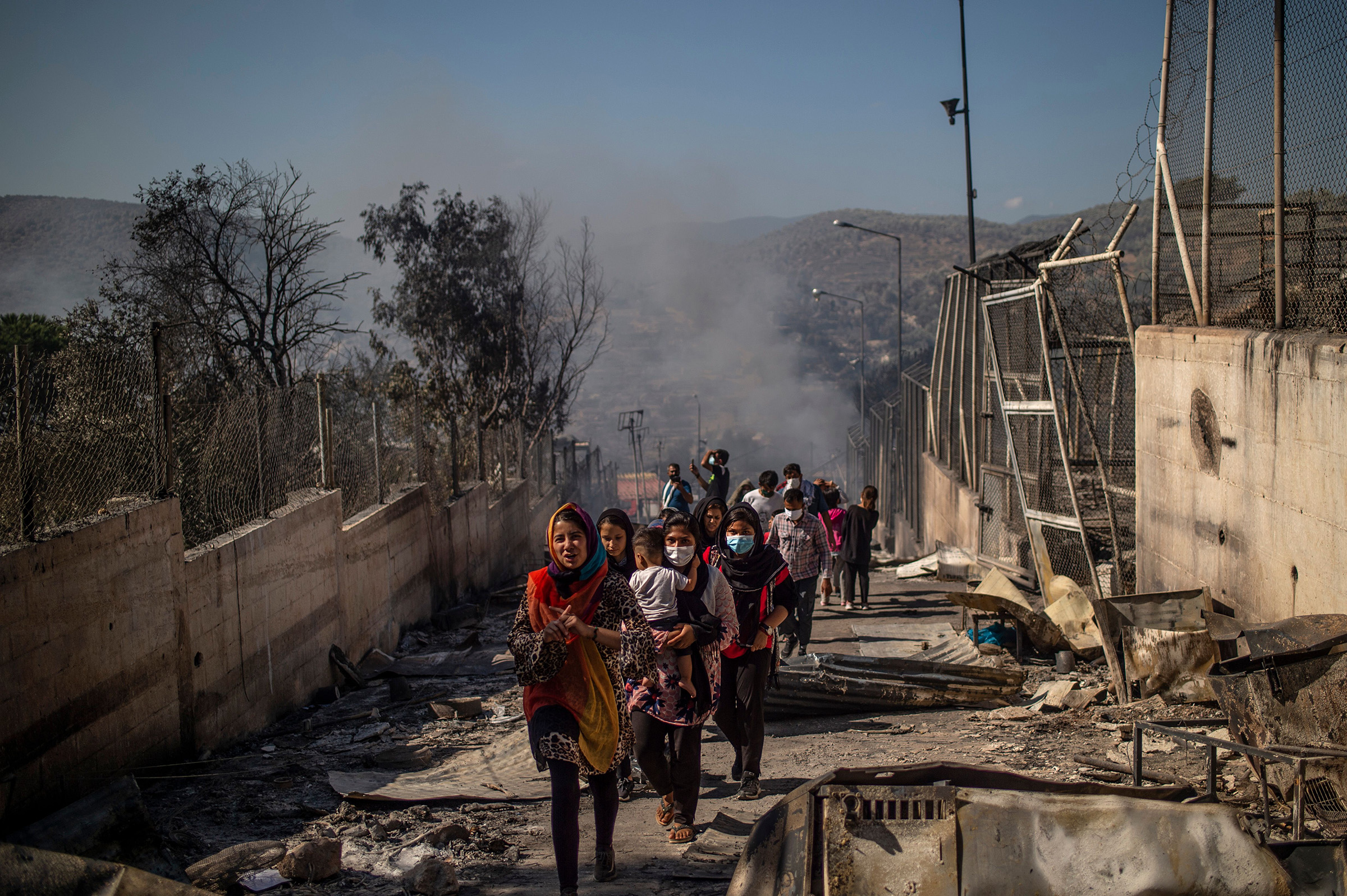 People walk in the burnt camp of Moria on the island of Lesbos after a major fire broke out, on Sept. 9, 2020.