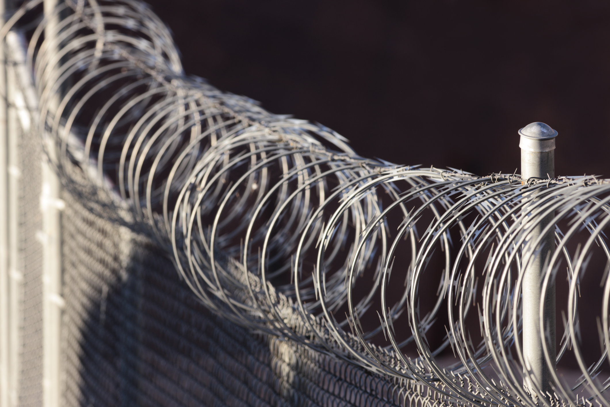 A razor wire topped fence runs diagonally from lower right to upper left of frame in a horizontal composition.