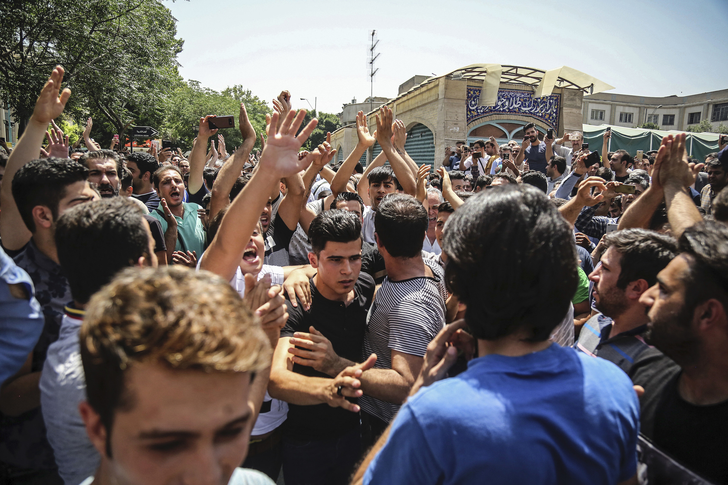 A group of protesters chant slogans at the main gate of the Old Grand Bazaar, in Tehran, Iran, on June 25, 2018.