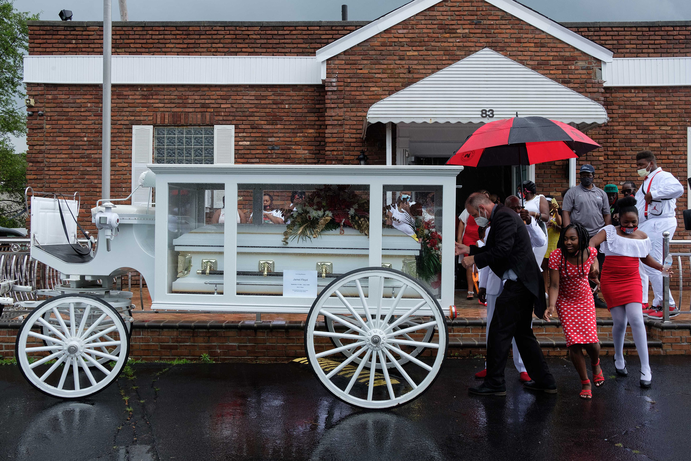 Jamel Floyd's coffin is placed in a horse carriage after the funeral.