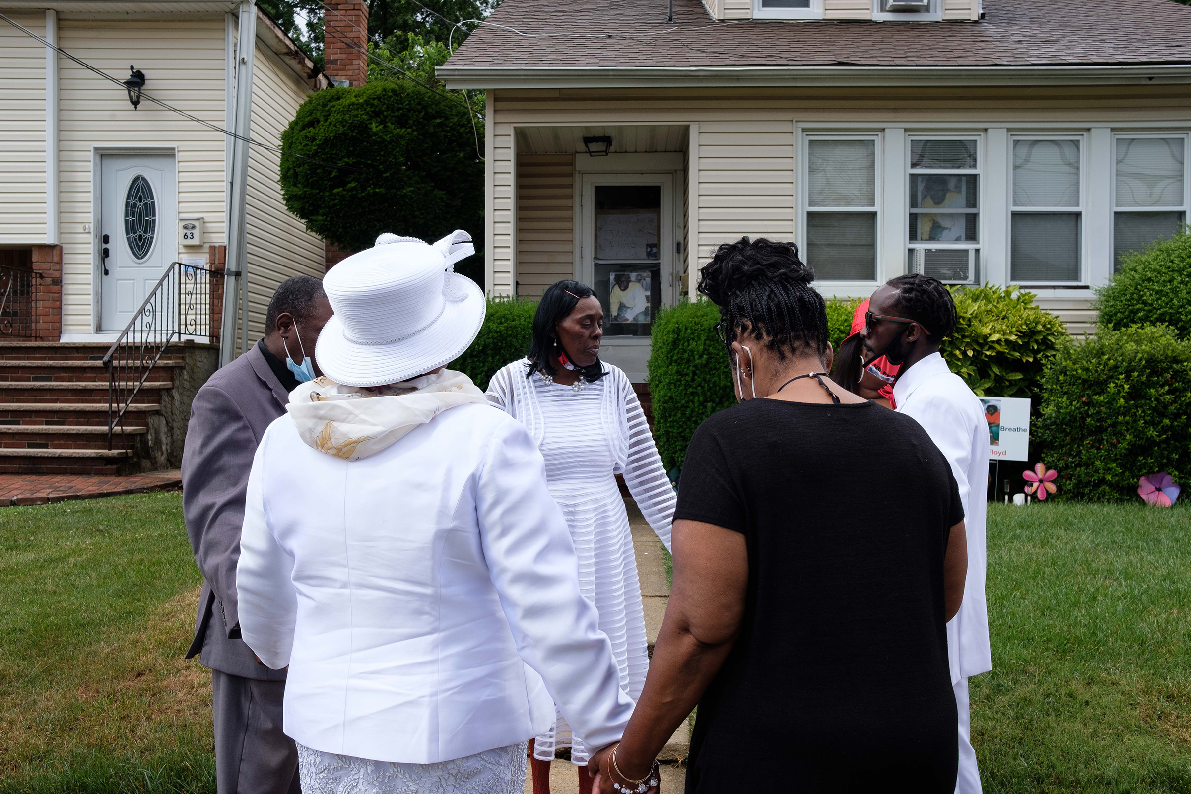 Family members stop to pray in front of his house during a procession from the church to Greenfield Cemetery in Hempstead, N.Y.