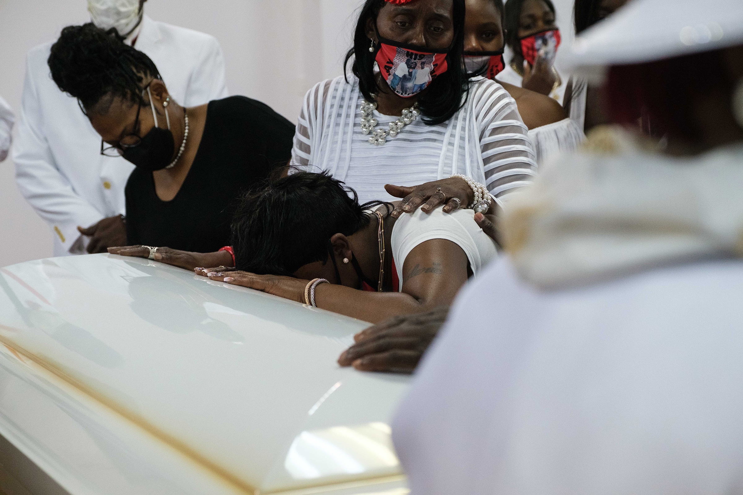 Family members comfort Jamel Floyd's sister Tawana Floyd during the funeral.