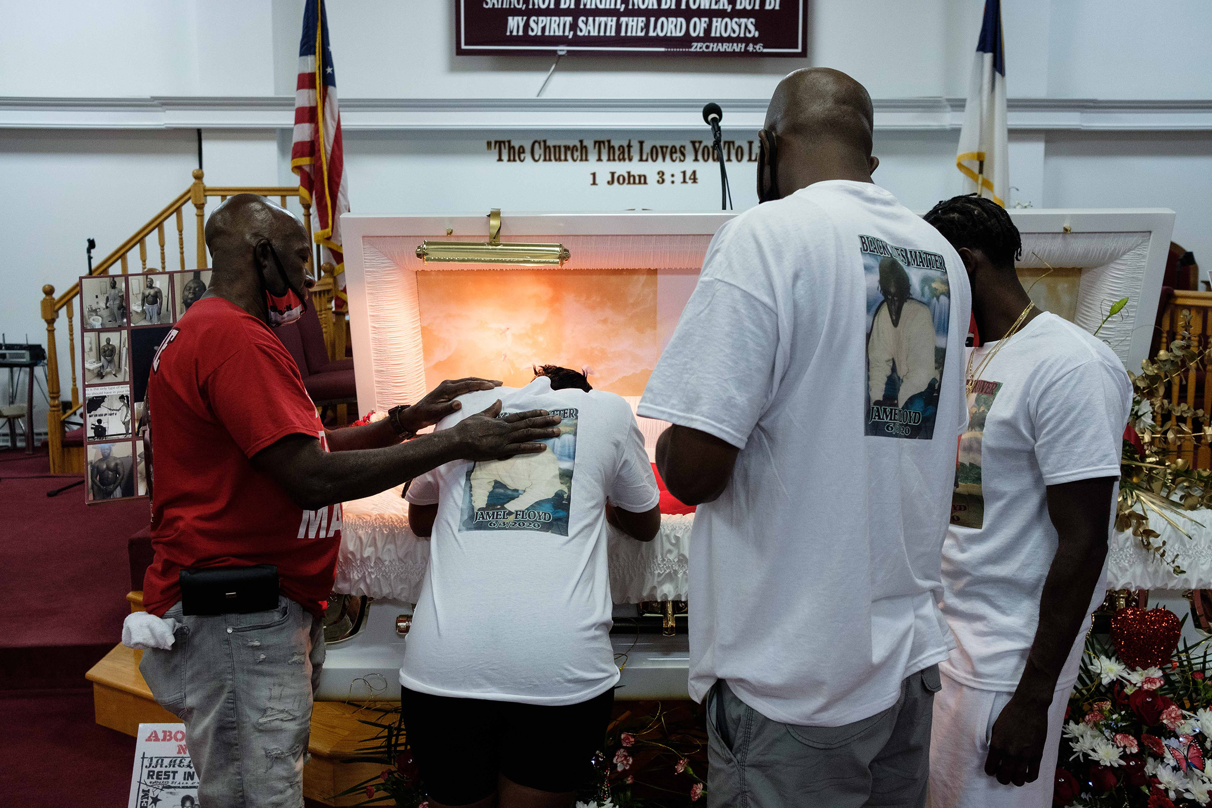 Ramel Floyd looks down at his older brother's body during the wake on June 29.
