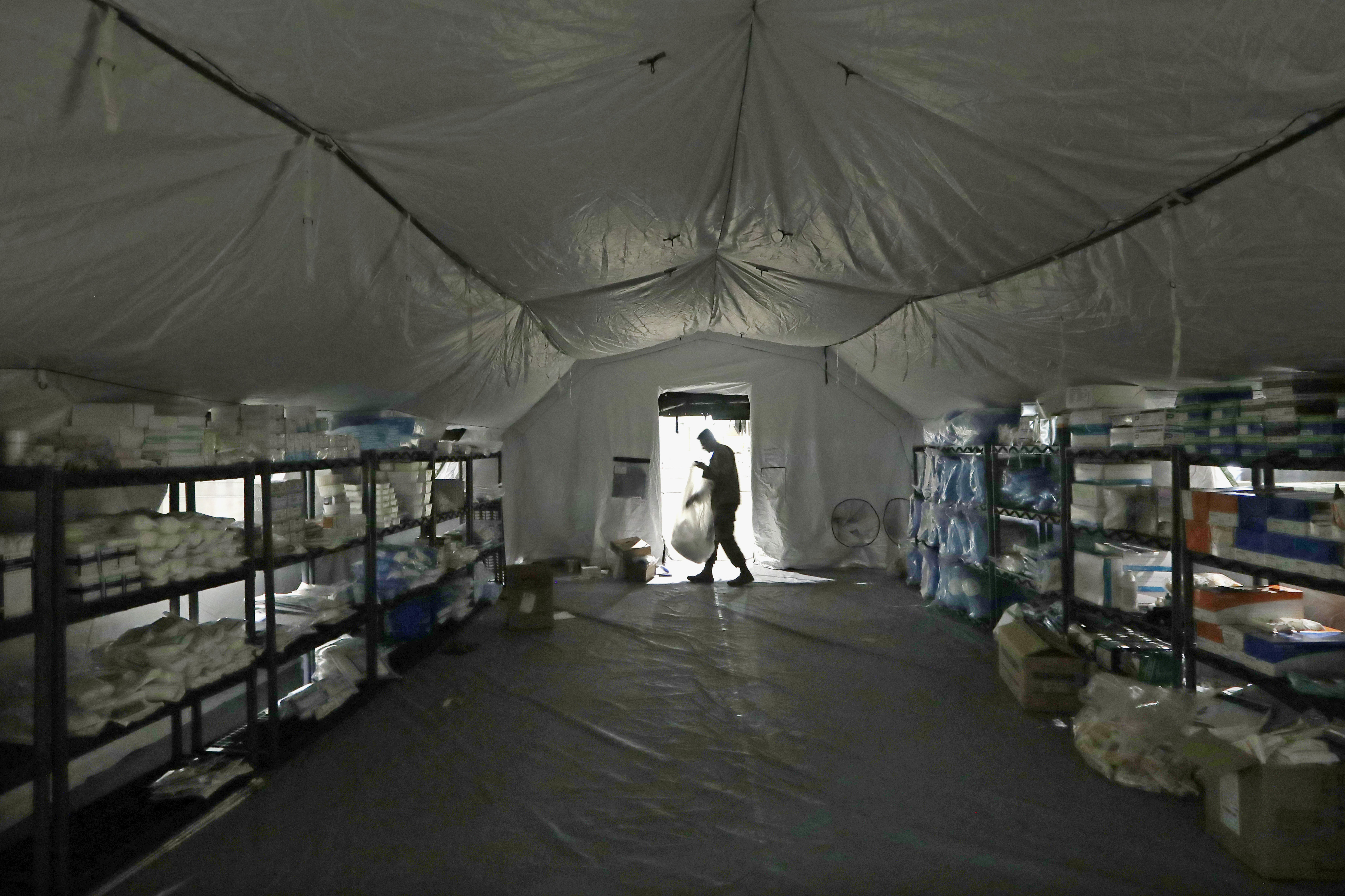 A U.S. Army soldier walks inside a mobile surgical unit being set up by soldiers from Fort Carson, Col., and Joint Base Lewis-McChord (JBLM) as part of a field hospital inside CenturyLink Field Event Center, in Seattle on March 31, 2020.