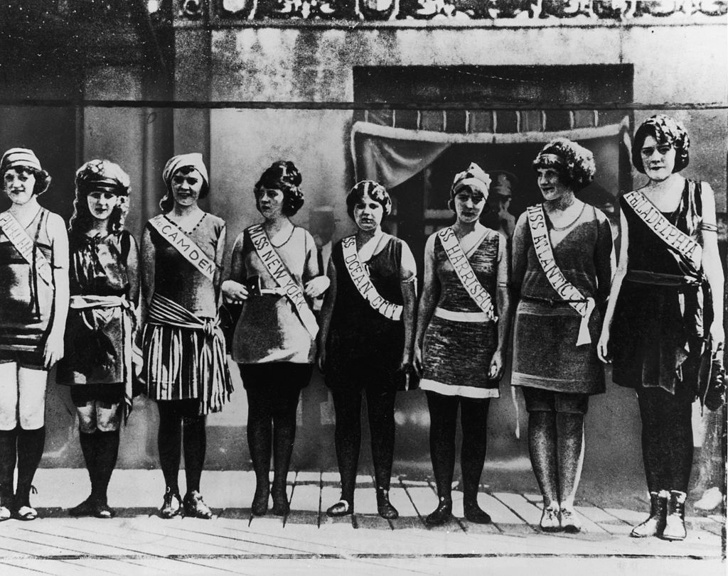 Portrait of the first Miss America contestants, wearing their sashes over swimsuits, standing in a line on the boardwalk in Atlantic City, N.J.