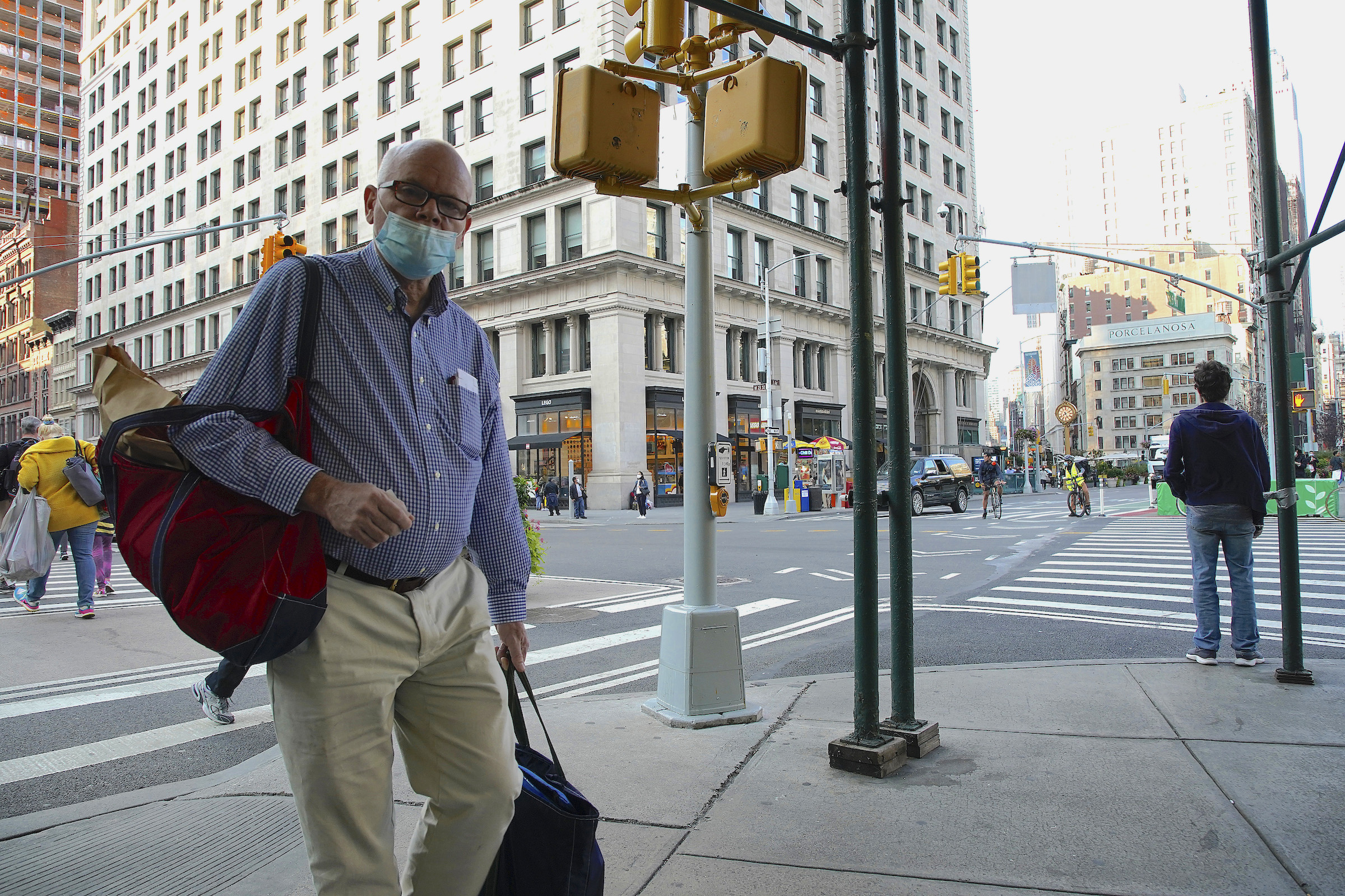 A man wearing a protective mask walks along the sidewalk in Madison Square during Phase 4 of re-opening following restrictions imposed to slow the spread of coronavirus on Sept. 22, 2020, in New York City