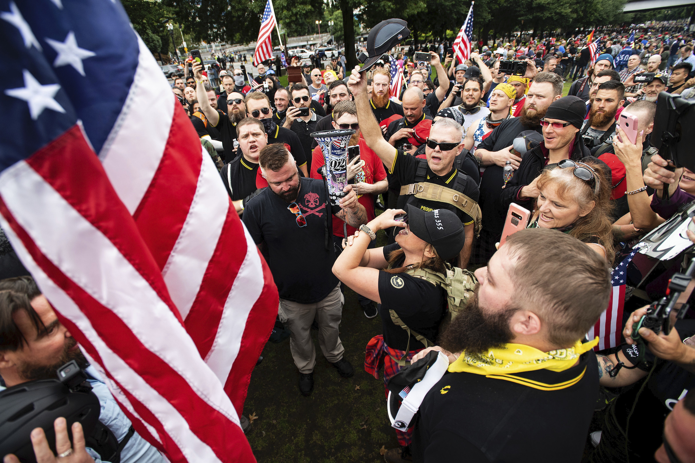Members of the Proud Boys and other right-wing demonstrators plant a flag in Tom McCall Waterfront Park during a rally in Portland, Ore on August 17, 2019.