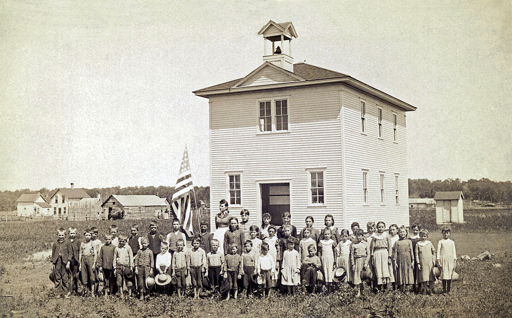 An American one room schoolhouse. with the class and teacher out front for their portrait, late 1880s or early 1890s