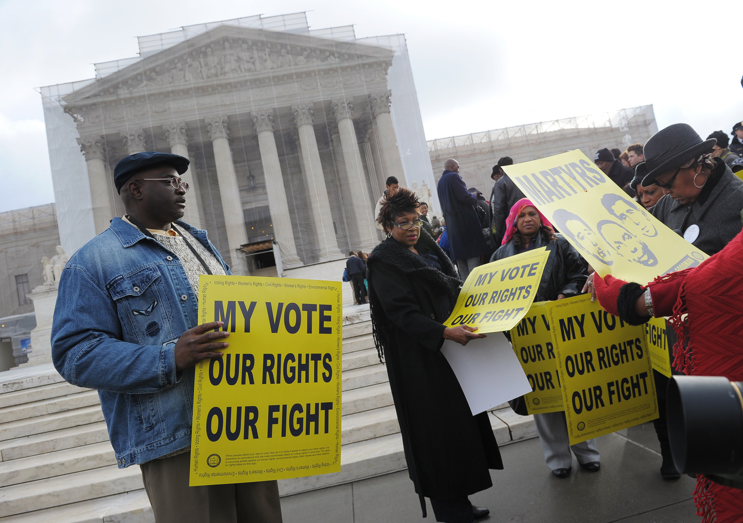 Activists distribute pro-voting rights placards outside the Supreme Court in Washington, D.C., on Feb. 27, 2013, as the Court prepares to hear Shelby County vs Holder.