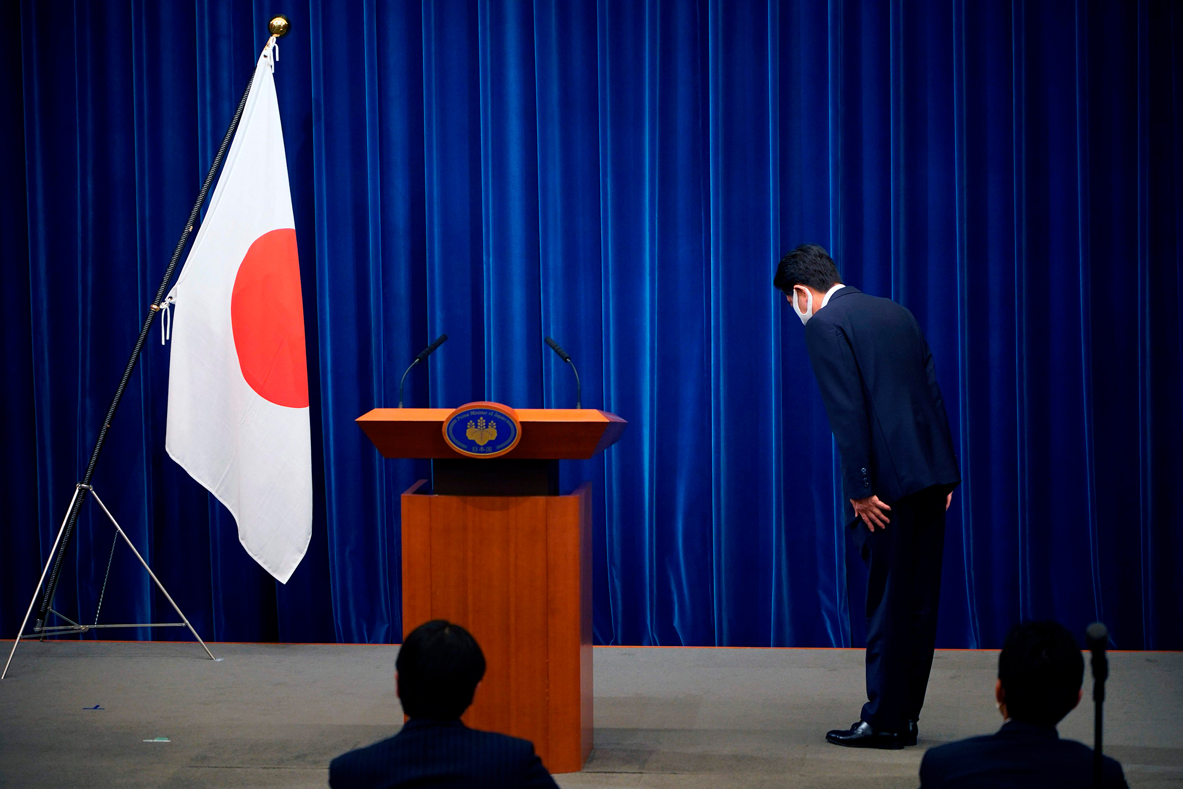 Japanese Prime Minister Shinzo Abe bows to the national flag at the start of a press conference announcing he will resign over health problems on August 28, at the prime minister's official residence in Tokyo
