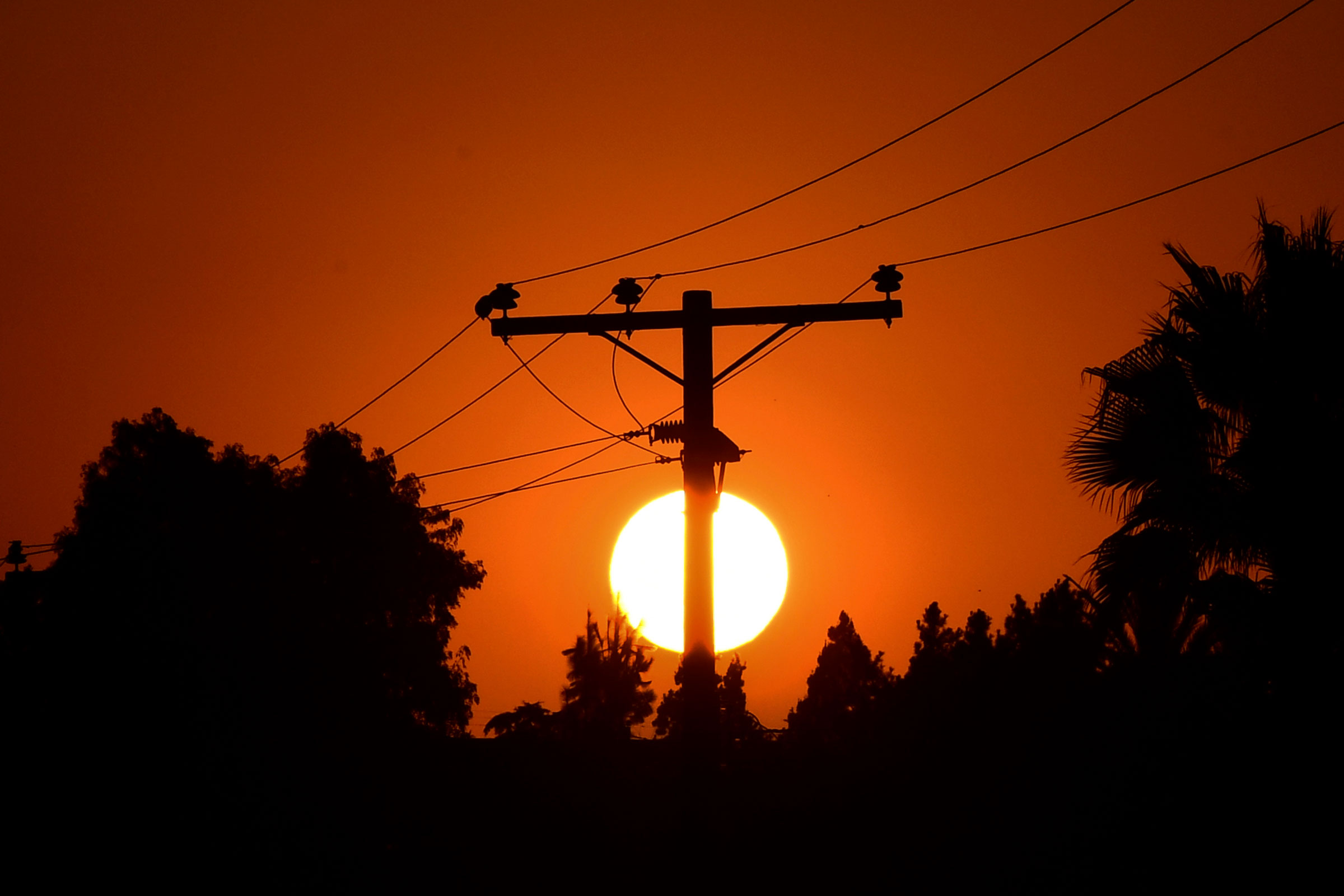 The sun sets behind power lines in Los Angeles, Calif. on Sept. 3, 2020.