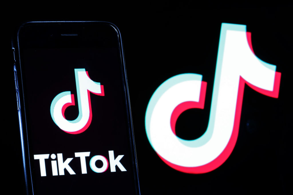PARIS, FRANCE - SEPTEMBER 15: In this photo illustration the logo of Chinese media app for creating and sharing short videos TikTok, also known as Douyin is displayed on the screen of a smartphone in front of a TV screen displaying the TikTok logo on September 15, 2020 in Paris, France. US software and hardware manufacturer Oracle Corporation confirmed Monday (September 14th) that it had made a proposal to take over the US operations of the Chinese video-sharing application TikTok, as the US government had announced earlier. The takeover of the American branch of the Chinese social network by an American company is at the heart of a battle between Washington and Beijing. (Photo by Chesnot/Getty Images)