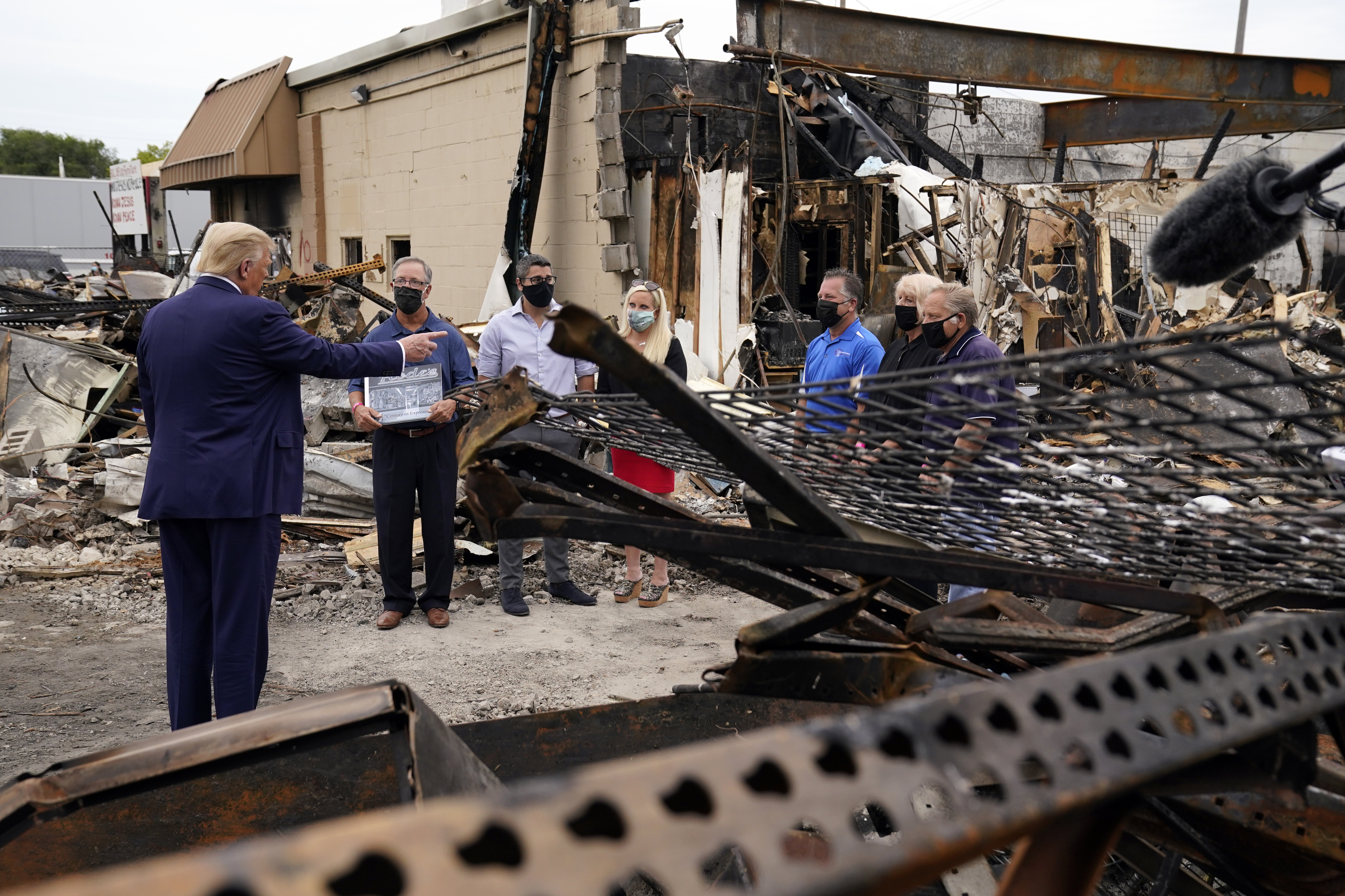 President Donald Trump talks to business owners as he tours an area damaged during demonstrations in Kenosha, Wis. on Sept. 1, 2020.