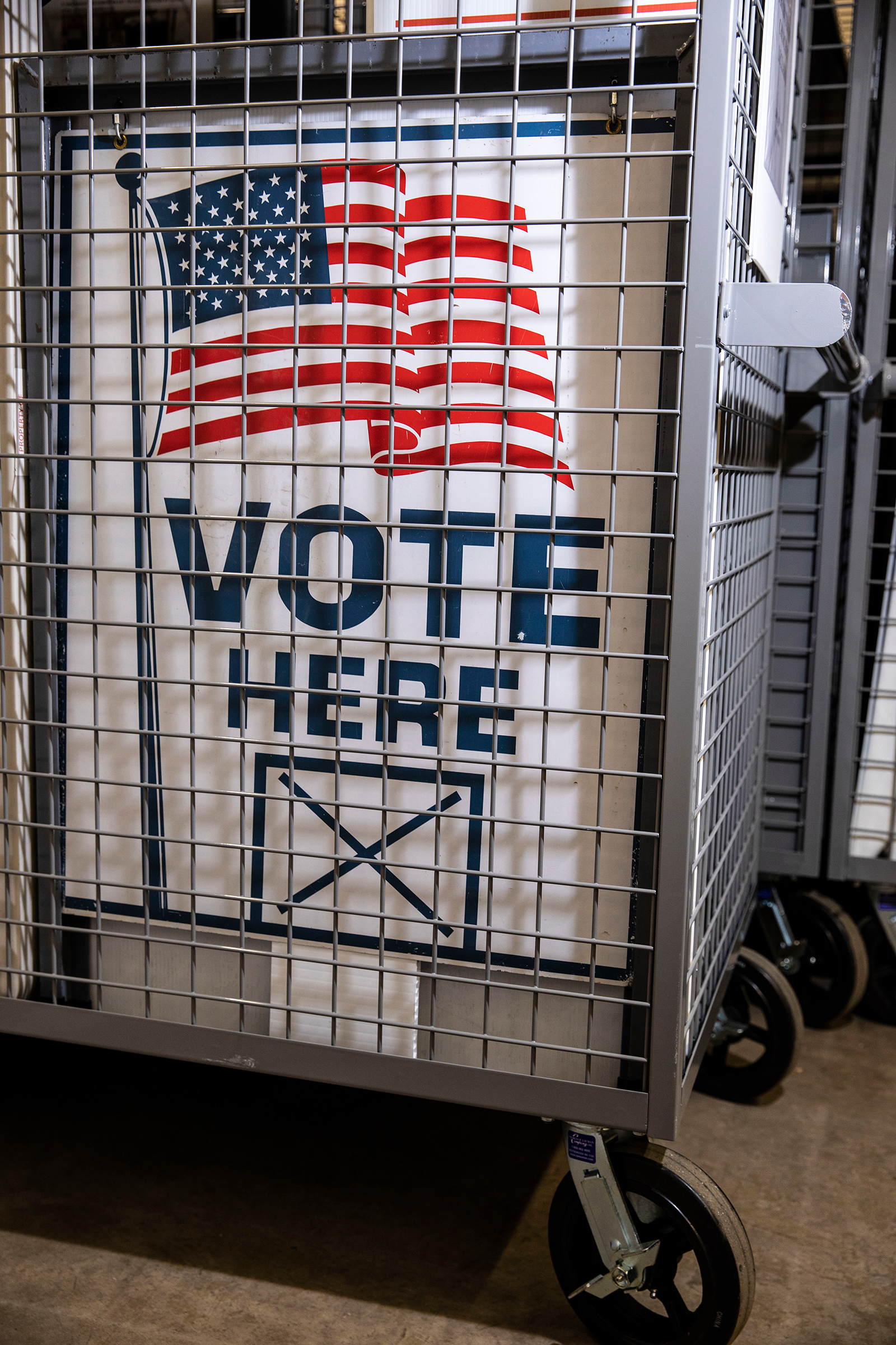 A locked cage at a secure county supervised storage facility on Sept. 8 in Davenport, IA, includes everything a precinct will need on election day, including a voting machine and signage thats all been prepped for delivery