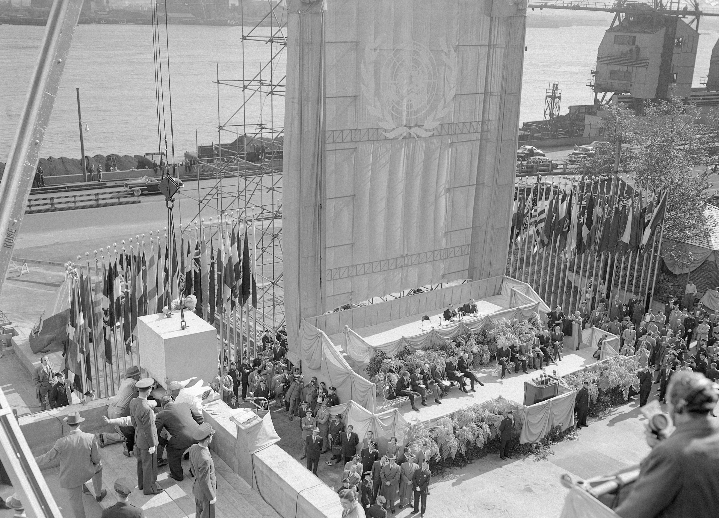 Secretary-General Tygve Lie (lower left), of Norway, stoops for a close view as workmen set the cornerstone at the new United Nations headquarters, Oct. 24, 1949. Looking up from the dais below are President Truman and other U.S. and foreign dignitaries. A huge U.N. flag, flanked by the colors of the 59 member nations, provides a backdrop.