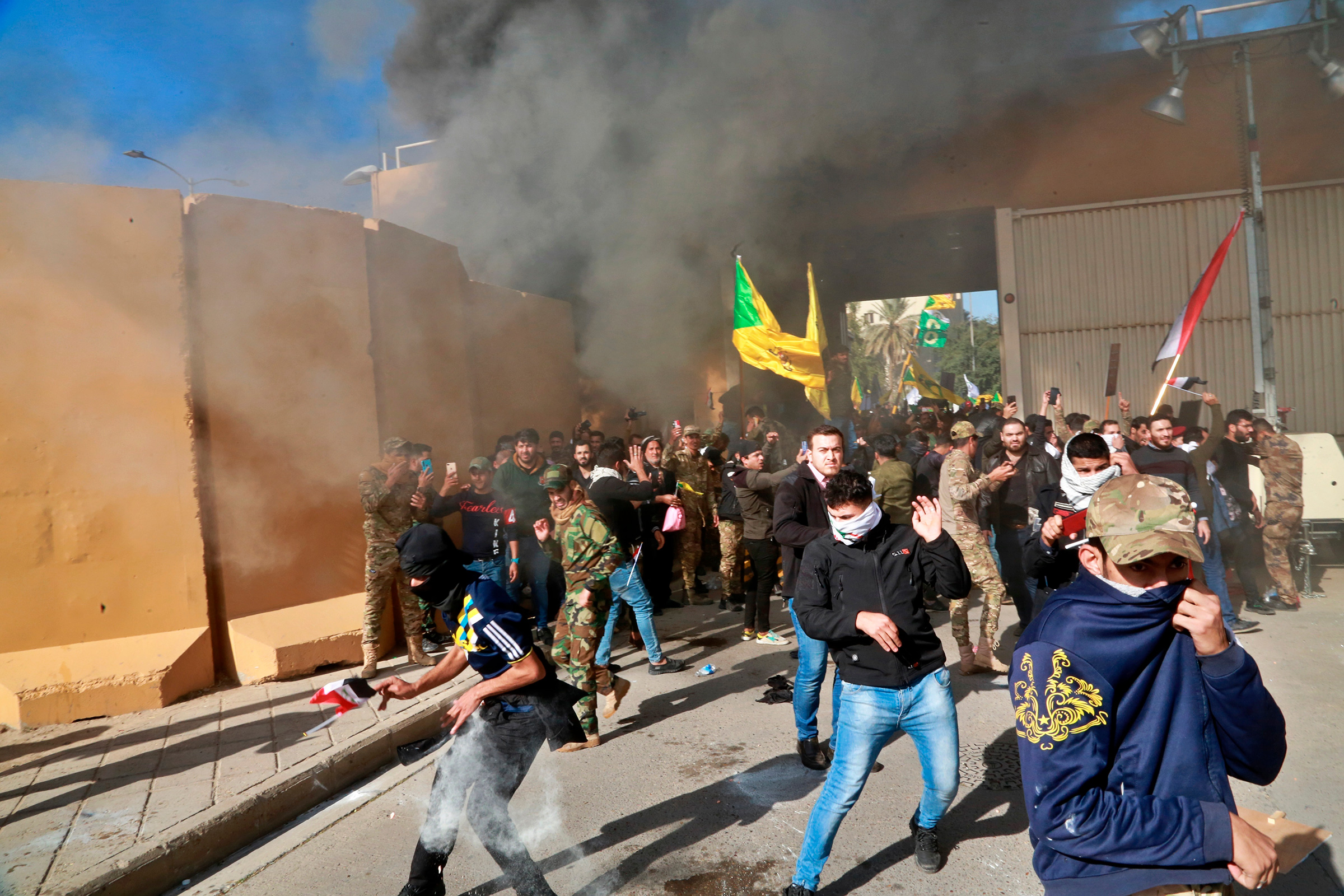 Protesters run from tear gas at the U.S. embassy compound in Baghdad, Dec. 31, 2019.