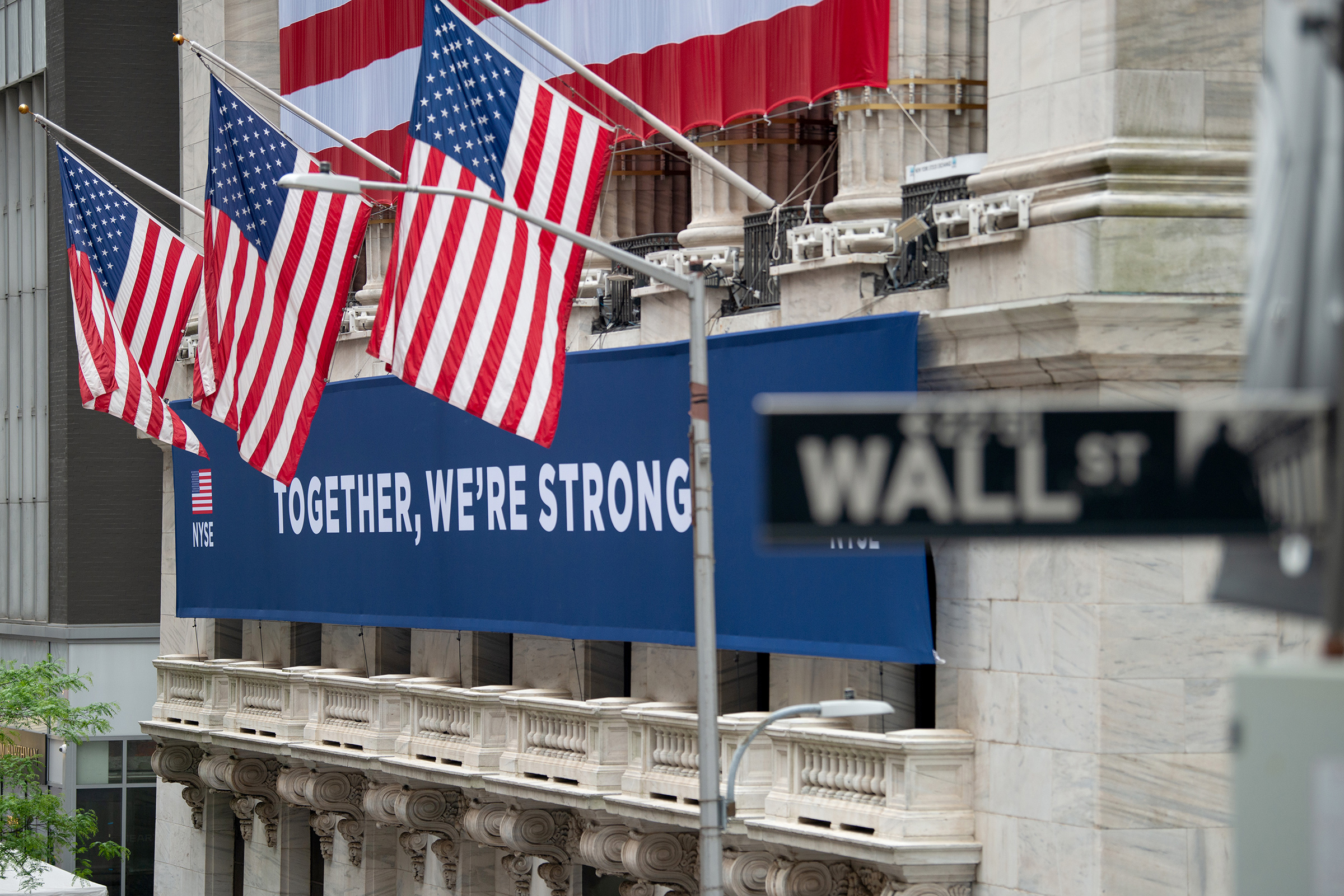 A view of the  Together, We're Strong  banner in front of the New York Stock Exchange on May 28