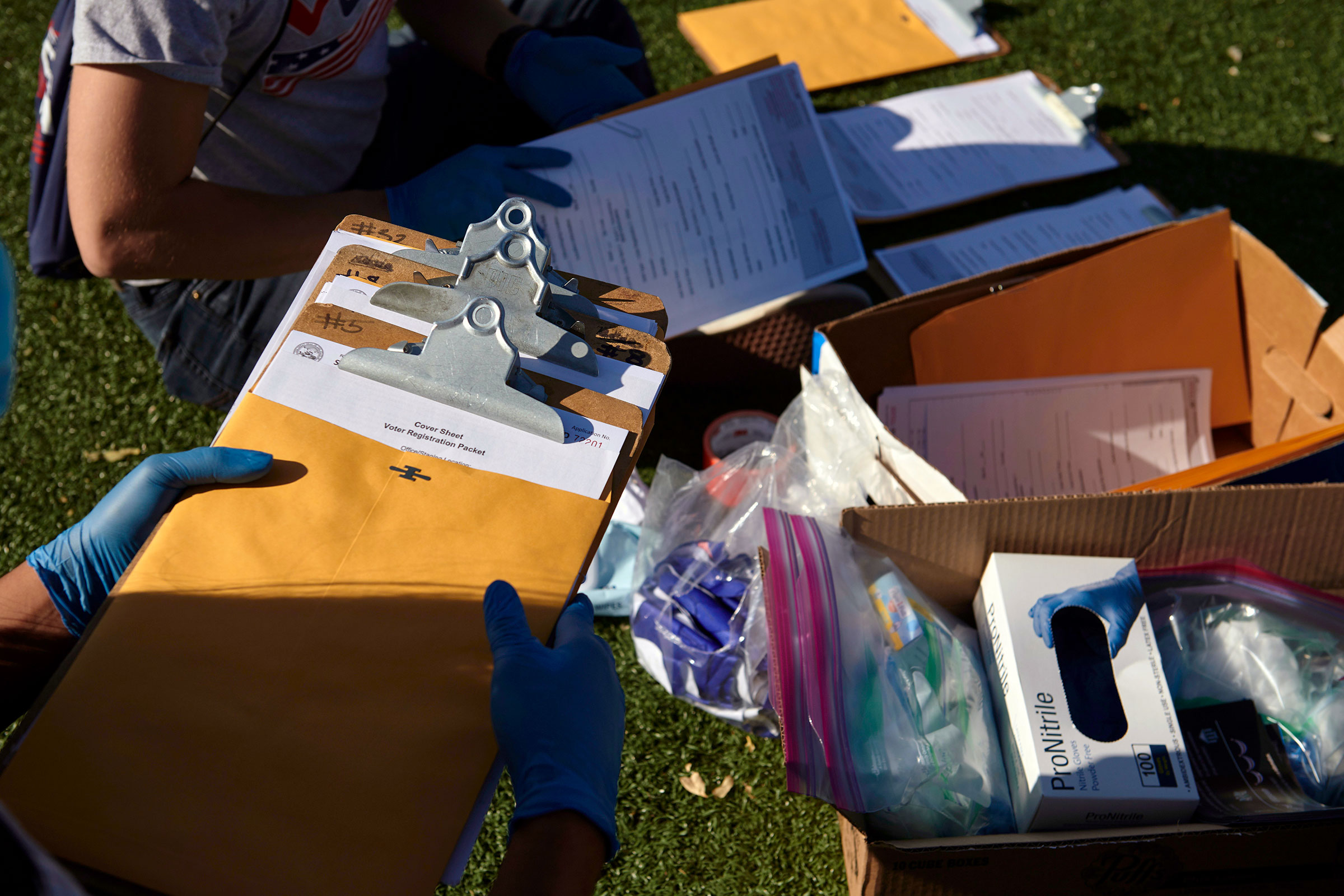 Mi Familia Vota workers organize their voter registration materials and personal protective equipment before canvassing in Las Vegas on Sept. 12, 2020.