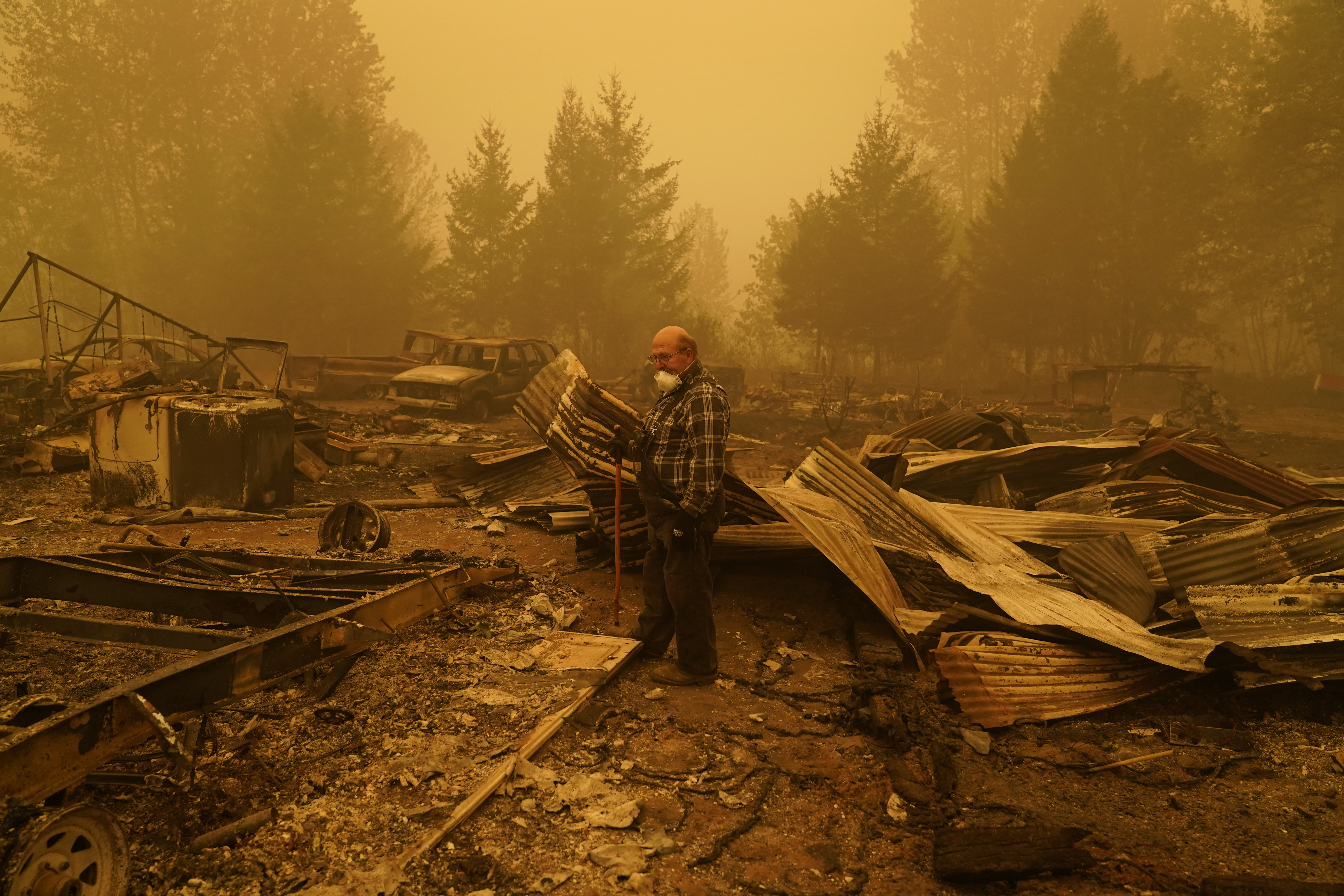 George Coble walks through what remains of a home on his property destroyed by a wildfire Sept. 12, 2020, in Mill City, Ore.