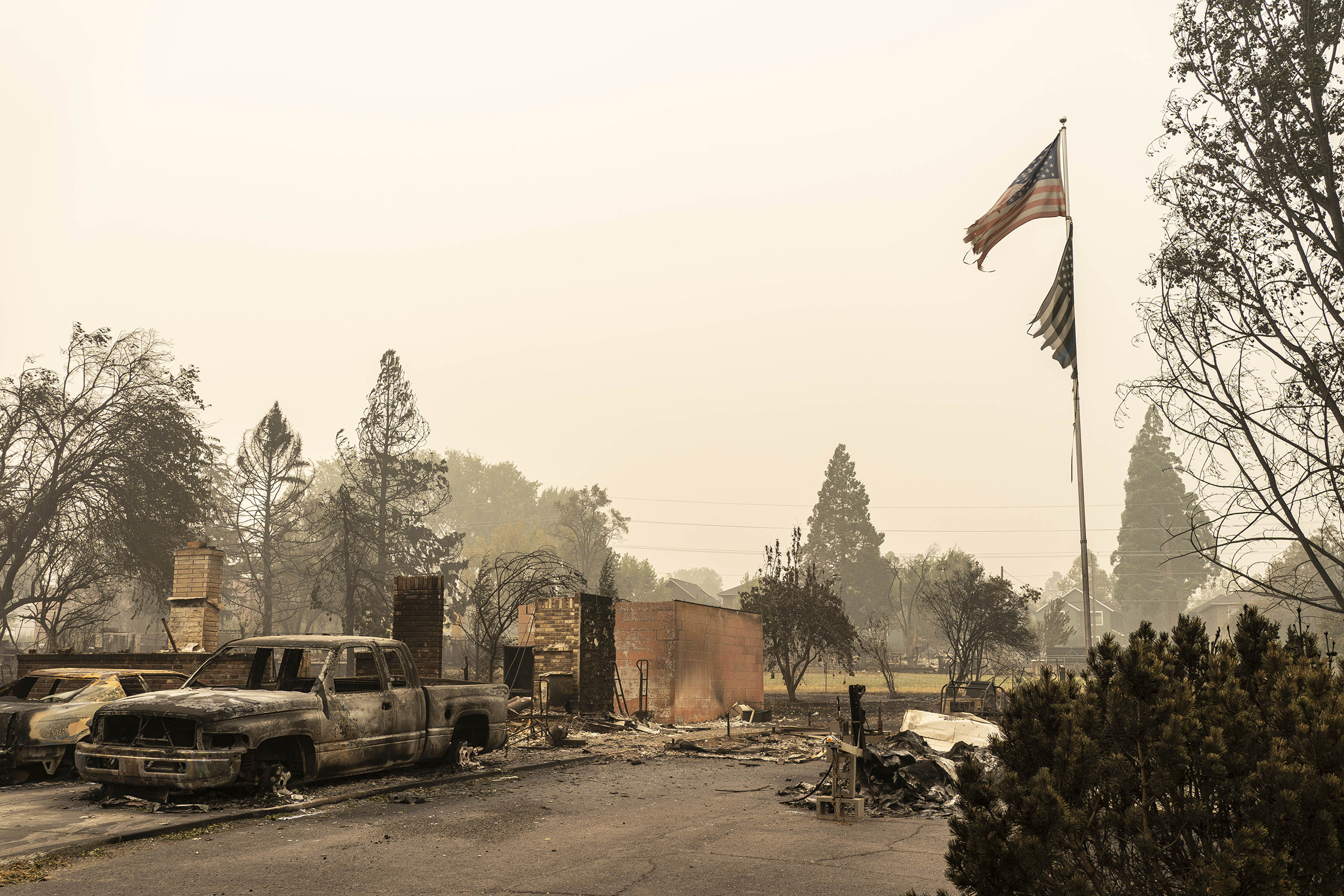 A U.S. flag flies at a burnt home in a neighborhood destroyed by wildfire on Sept. 13 in Talent, OR