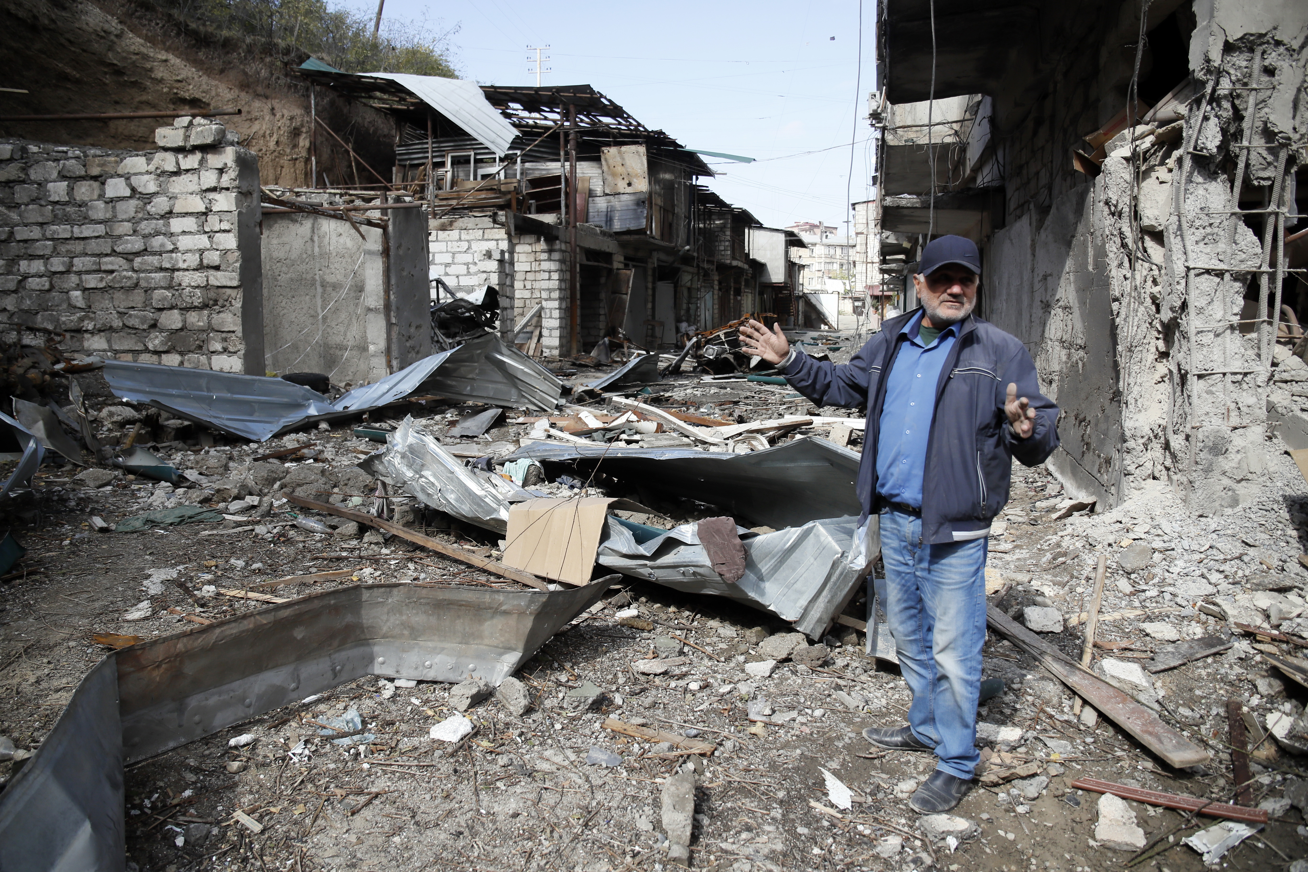 Eduard Chechyan gestures in the yard of his apartment building, destroyed by shelling by Azerbaijan's artillery, during a military conflict in Stepanakert, the separatist region of Nagorno-Karabakh, Oct. 10, 2020.