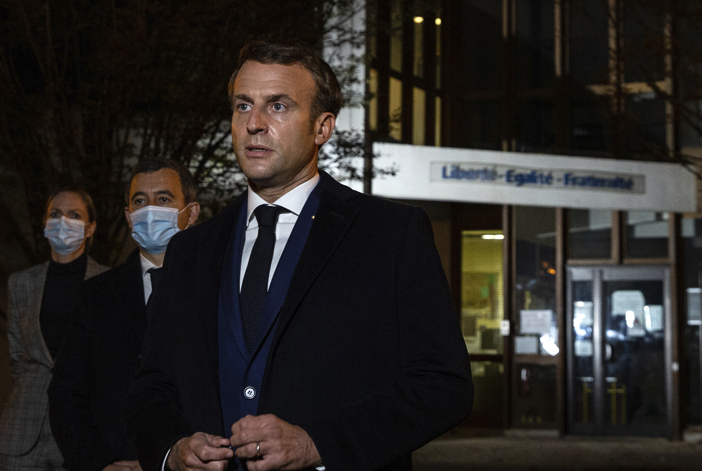 French President Emmanuel Macron, flanked by French Interior Minister Gerald Darmanin, second left, speaks in front of a high school Oct.16, 2020 in Conflans Sainte-Honorine.