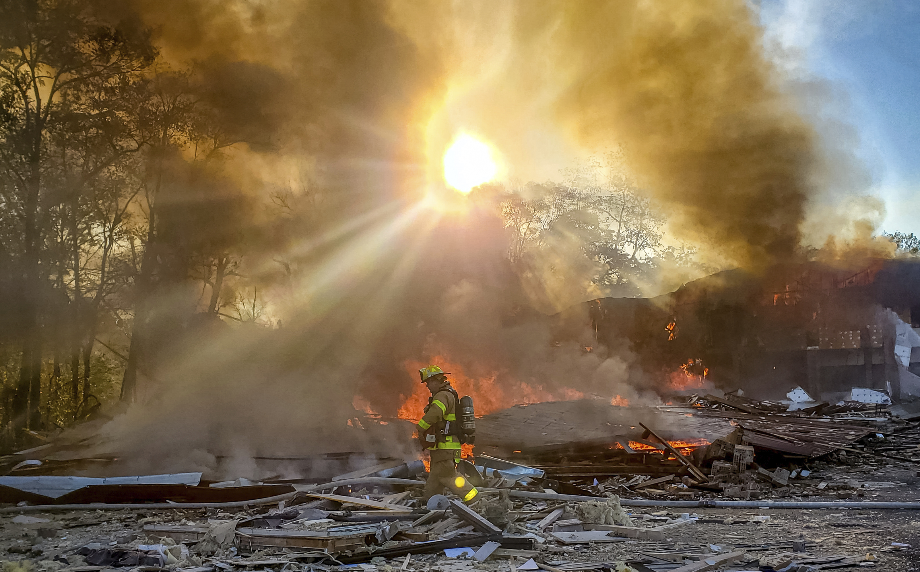 A firefighter walks through the burning rubble of a shopping center after an explosion in Harrisonburg, Va., on Oct. 17, 2020.