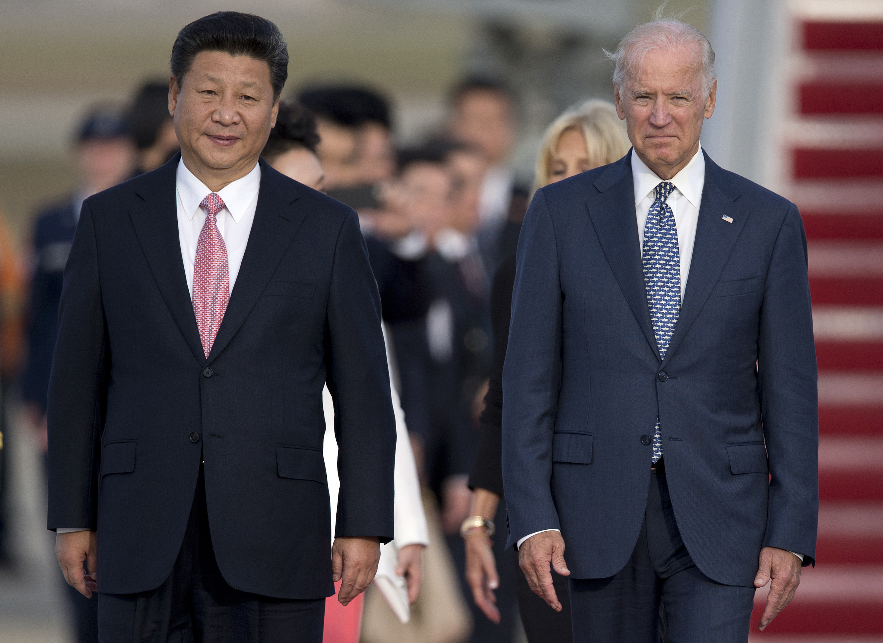 In this Sept. 24, 2015 file photo, Chinese President Xi Jinping and Vice President Joe Biden walk down the red carpet on the tarmac during an arrival ceremony in Andrews Air Force Base, Md.