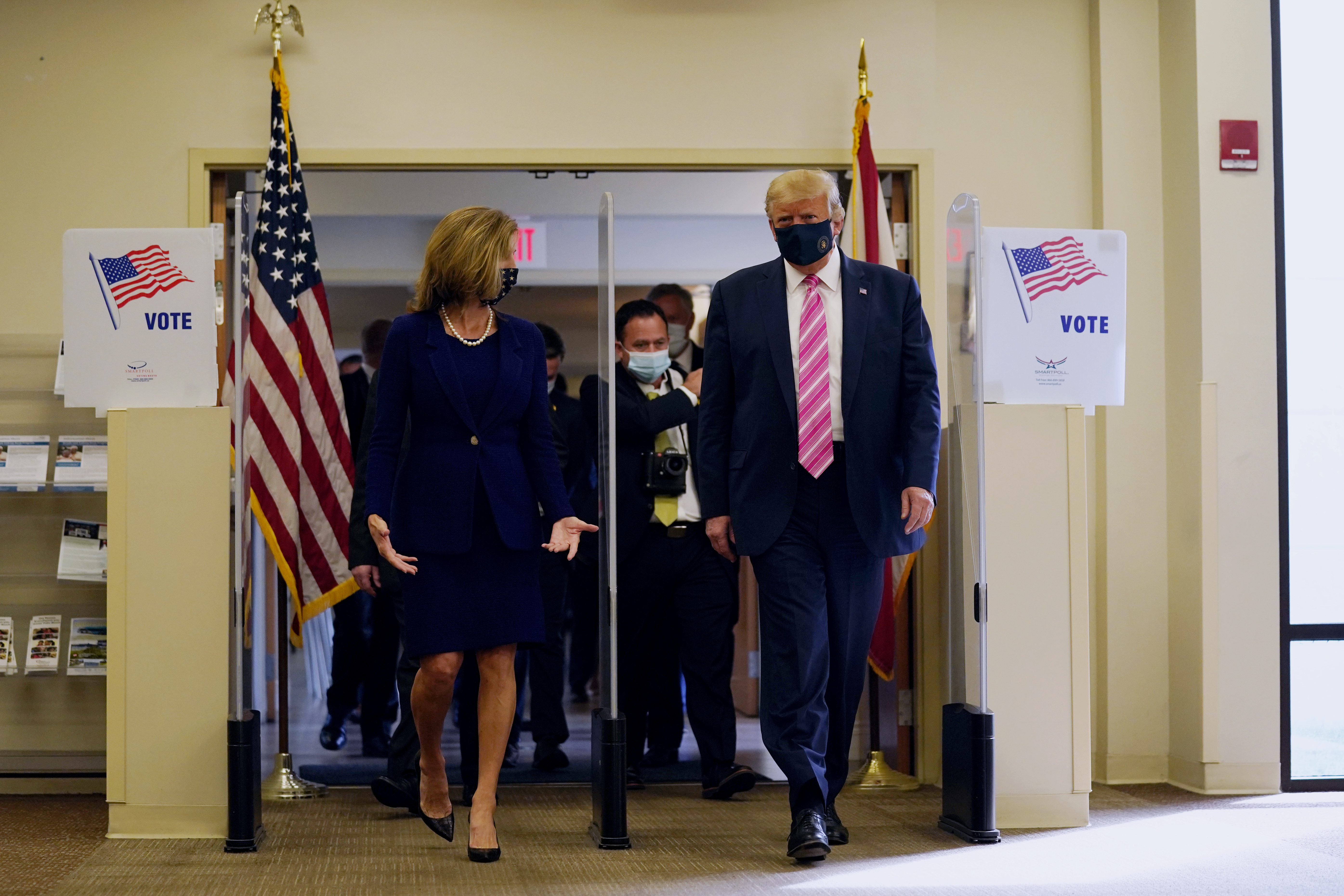 President Donald Trump walks with Wendy Sartory Link, Supervisor of Elections Palm Beach County, after casting his ballot for the presidential election in West Palm Beach, Fla., on on Oct. 24, 2020.