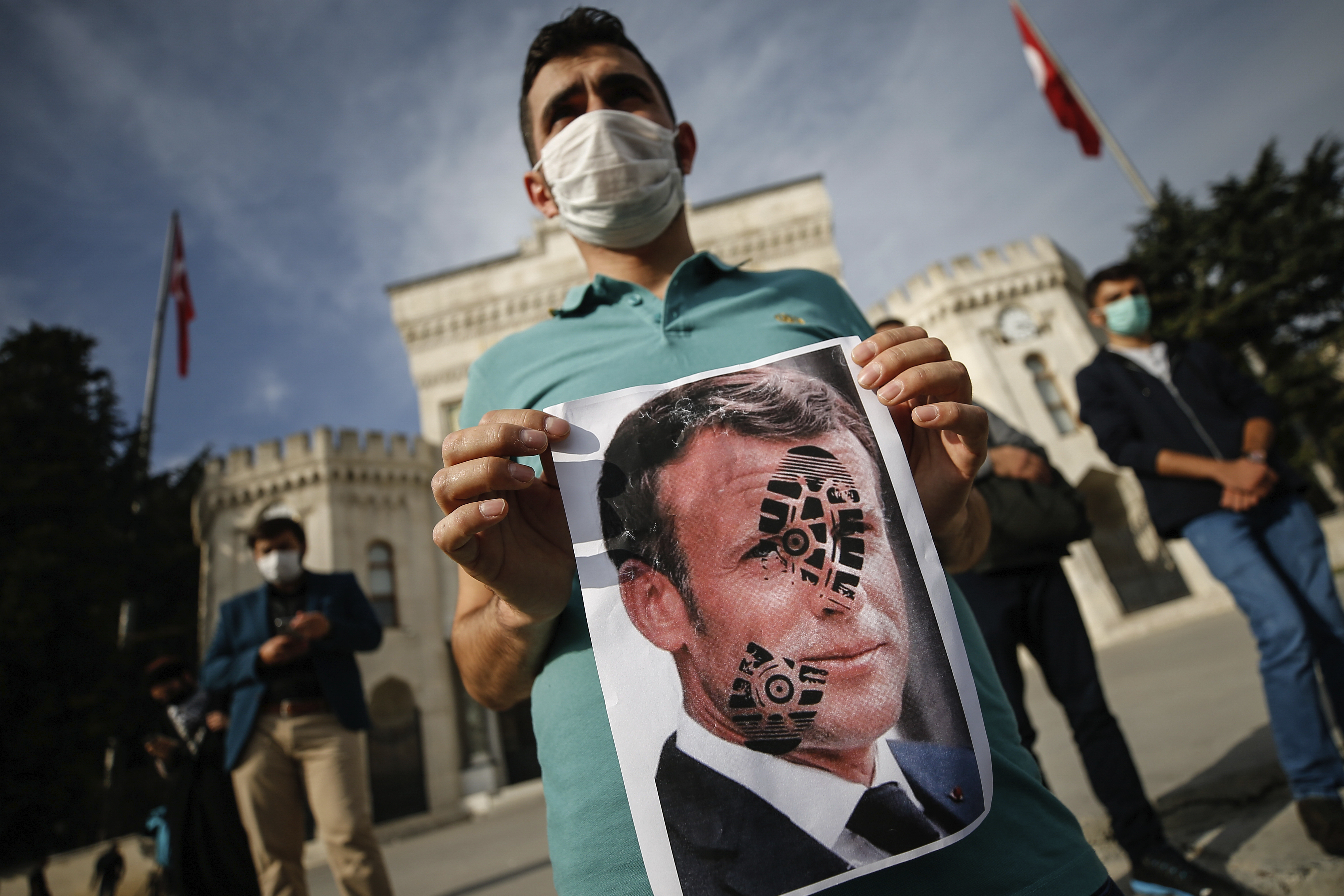 A youth holds a photograph of France's President Emmanuel Macron, stamped with a shoe mark, during a protest against France in Istanbul, Sunday, Oct. 25, 2020.