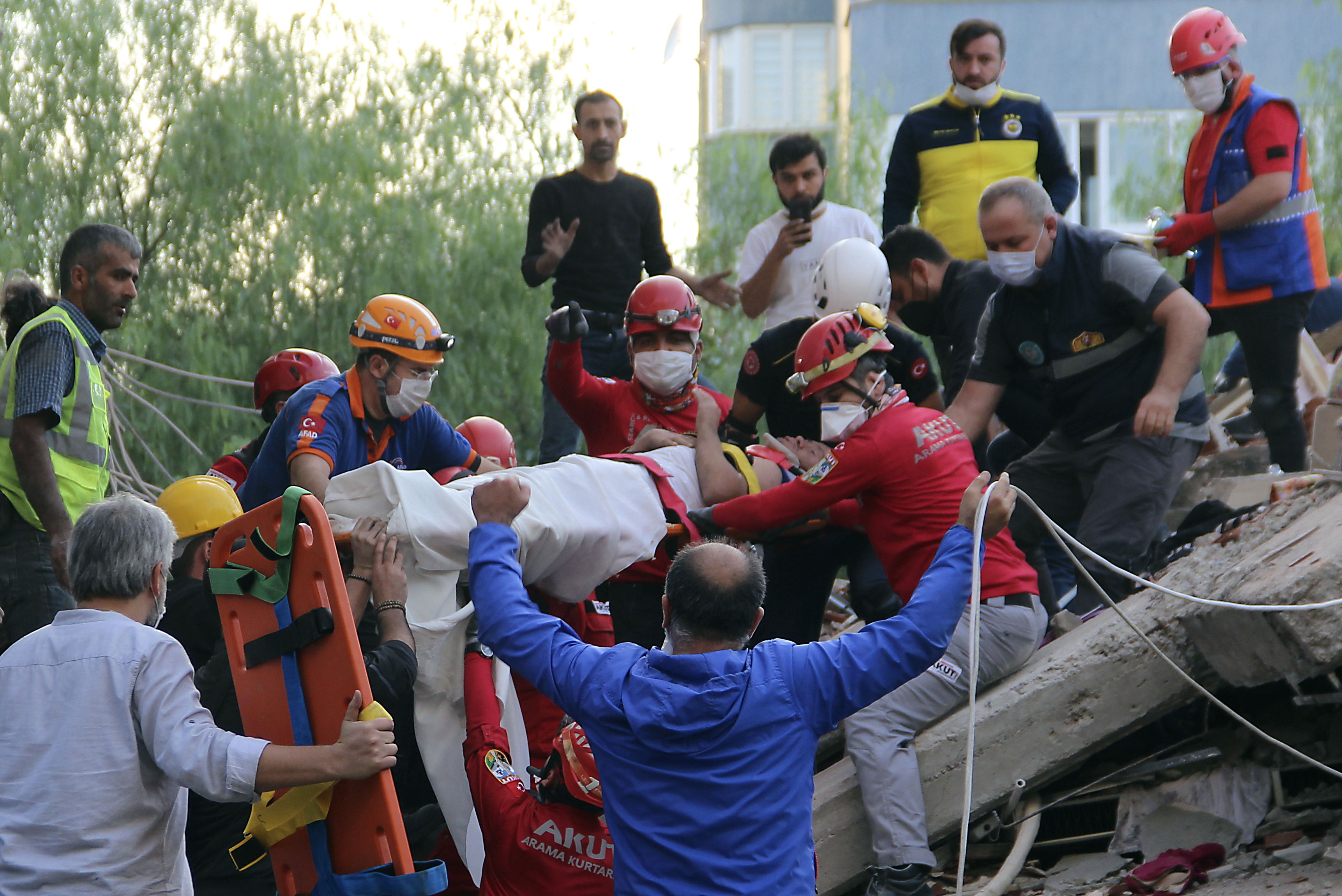 Rescuers carry a man rescued from the debris of his collapsed house, in Izmir, Turkey, on Oct. 30, 2020.