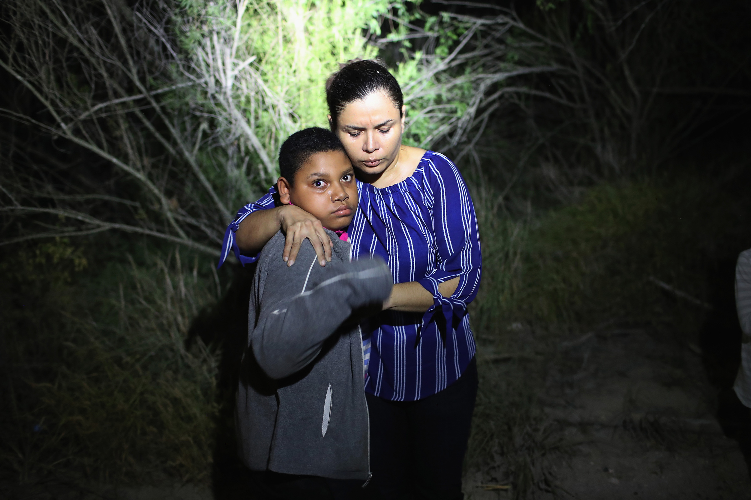 A U.S. Border Patrol spotlight shines on a mother and son from Honduras as they are found in the dark near the U.S.-Mexico border in McAllen, Texas on June 12, 2018. The asylum seekers were then detained by Border Patrol agents and then sent to a processing center for possible separation as part of the Trump Administration's  zero tolerance  policy towards undocumented immigrants.