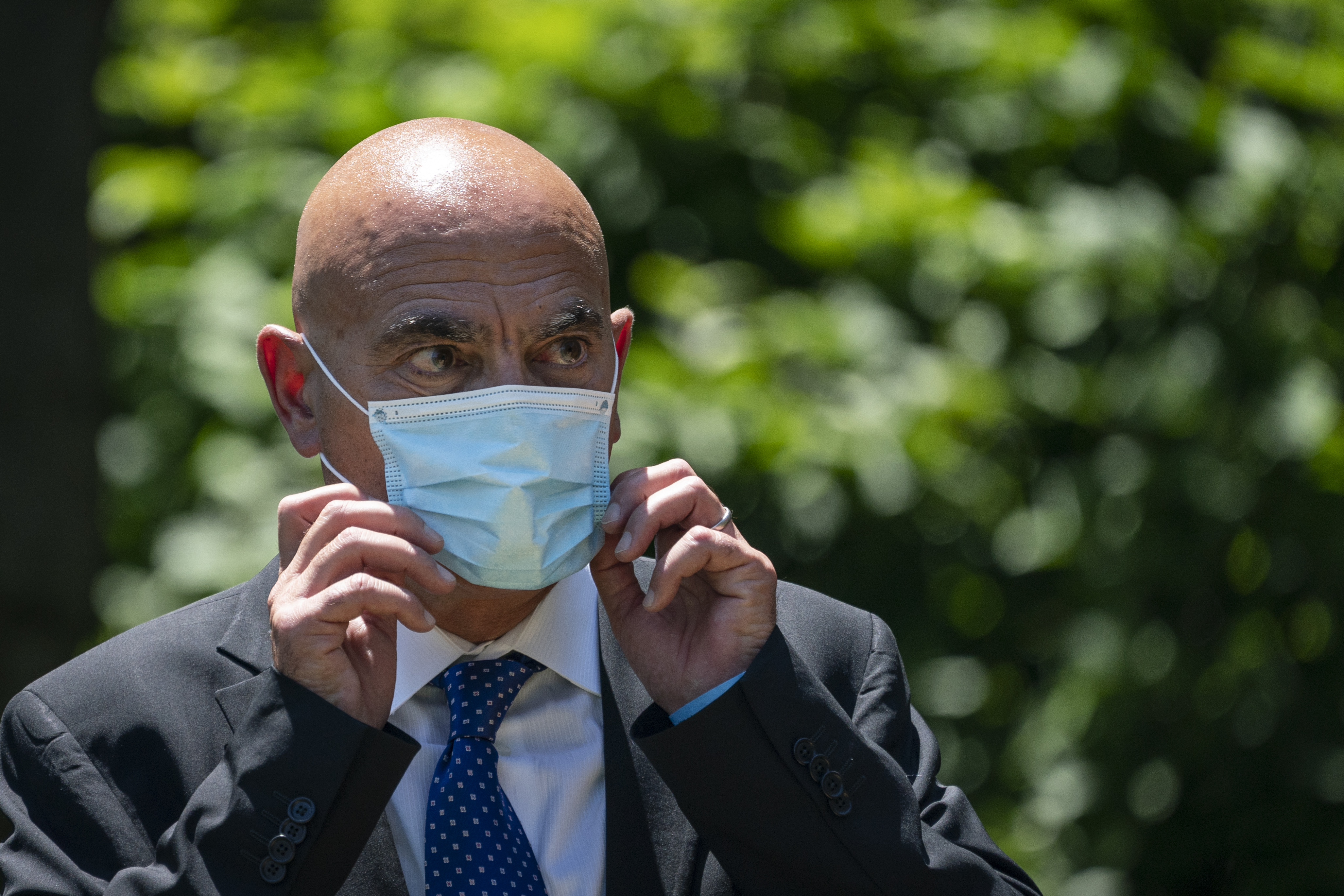 Moncef Slaoui, head of the White House's  Operation Warp Speed  project to develop a coronavirus vaccine, listens to U.S. President Donald Trump deliversremarks about vaccine development in the Rose Garden of the White House on May 15, 2020 in Washington, DC.