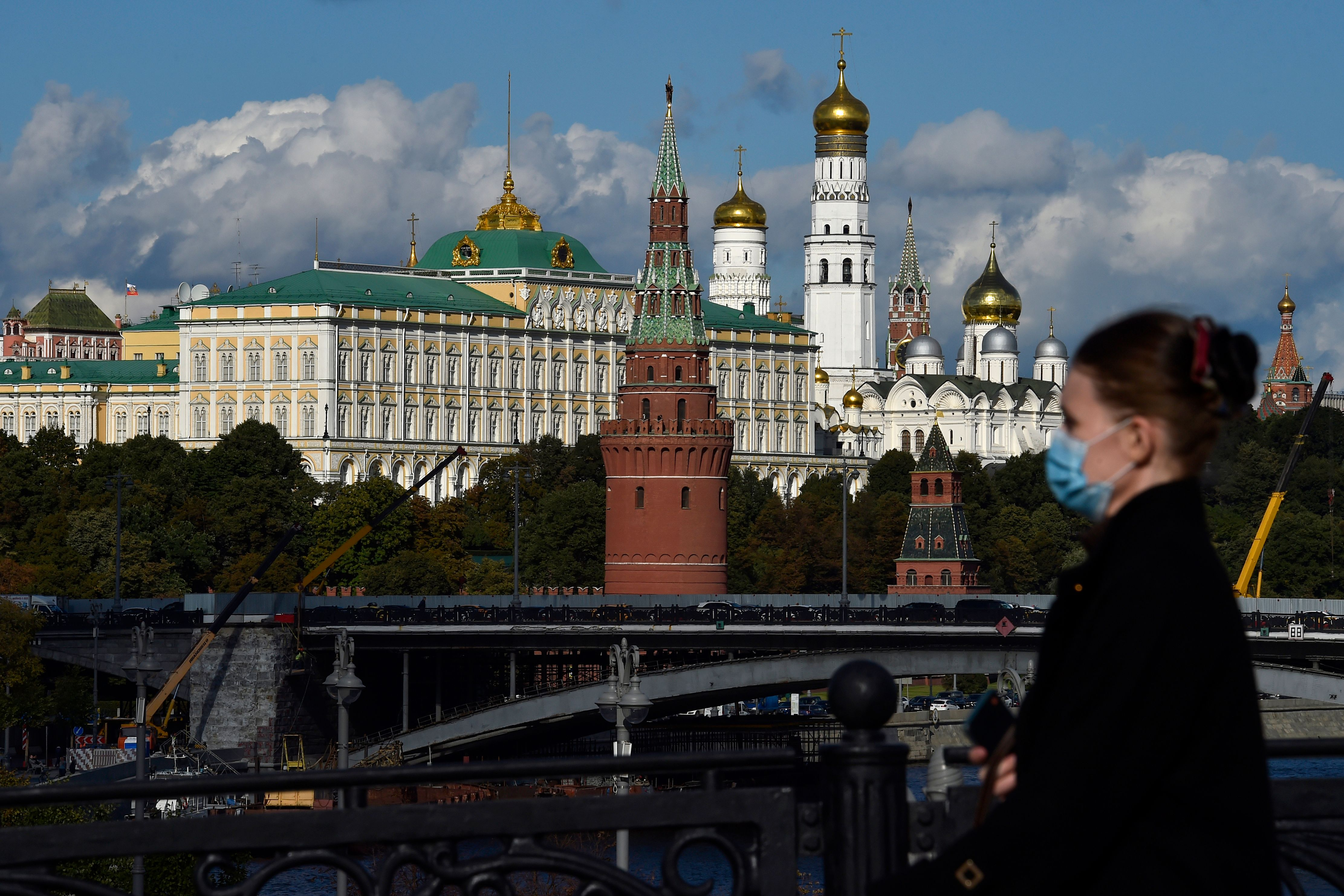 A woman wearing a face mask to protect against the coronavirus disease walks in downtown Moscow, with the Kremlin seen in the background, on Sept. 15, 2020.