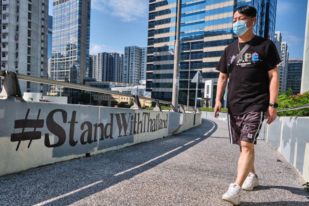A man wearing a face mask walks past  #StandWithThailand  graffiti in Hong Kong on Oct. 18, 2020.