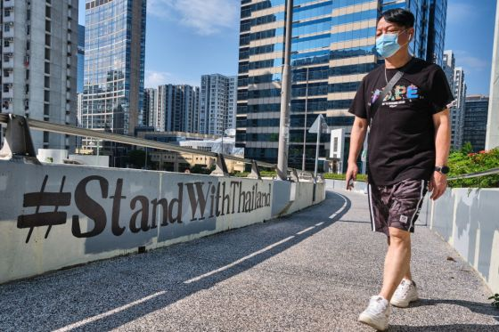 "A man wearing a facemask walks past a ""#StandWithThailand"""
