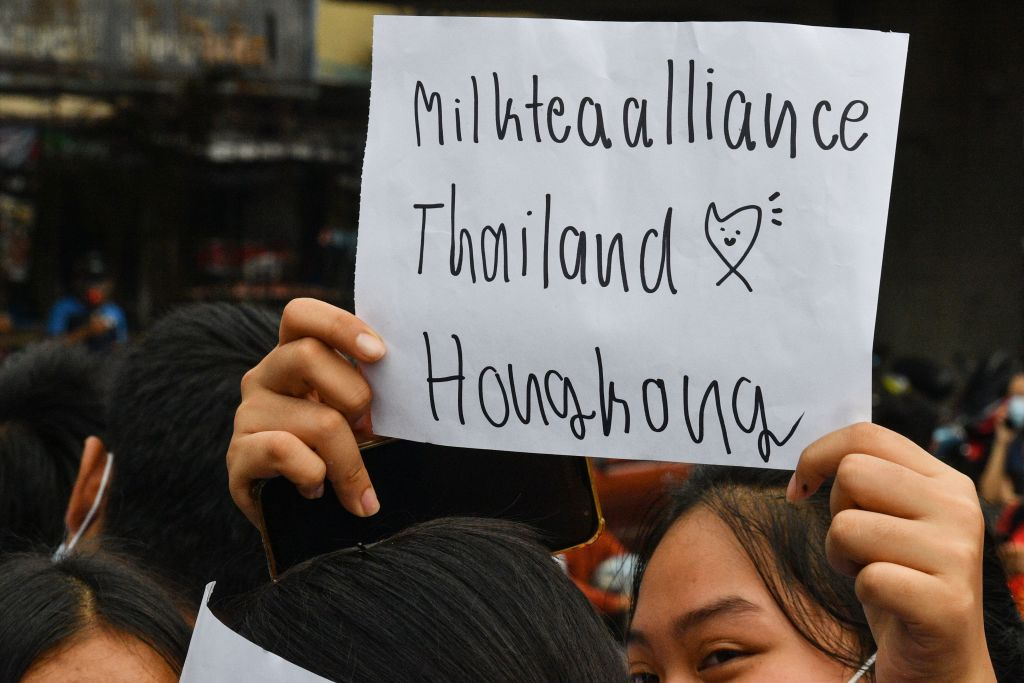 A pro-democracy protester holds up a sign relating to the  Milk Tea Alliance  during an anti-government rally at Kaset intersection in Bangkok on October 19, 2020